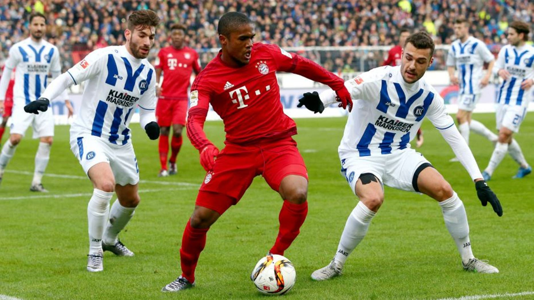 KARLSRUHE, GERMANY - JANUARY 16: Douglas Costa (C) of Muenchen is challenged by Enrico Valentini (L) and Manuel Gulde of Karlsruhe during a friendly match between Karlsruher SC and FC Bayern Muenchen at Wildpark Stadium on January 16, 2016 in Karlsruhe, Germany. (Photo by Alex Grimm/Bongarts/Getty Images)
