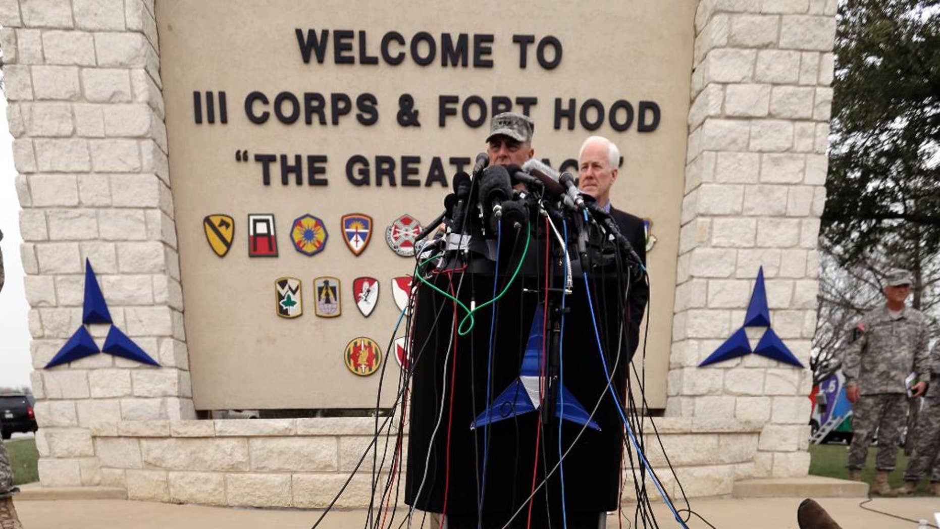 Lt. Gen. Mark Milley, left,and U.S. Sen. John Cornyn, right, talk to the media near Fort Hood's main gate, Thursday, April 3, 2014, in Fort Hood, Texas. A soldier opened fire Wednesday on fellow service members at the Fort Hood military base, killing three people and wounding 16 before committing suicide. (AP Photo/Eric Gay)