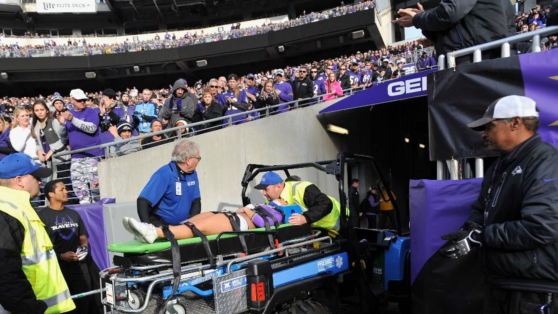 A Baltimore Ravens cheerleader is taken off the field after being injured during the second half of an NFL football game against the Tennessee Titans in Baltimore, Sunday, Nov. 9, 2014. (AP Photo/Gail Burton)