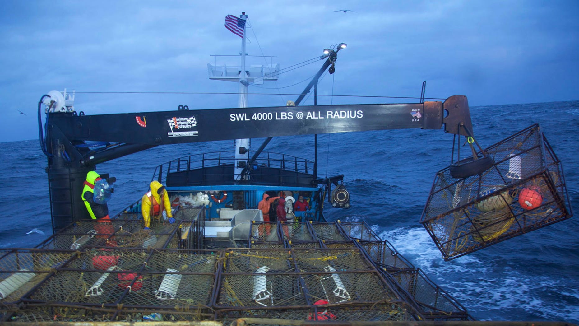 """This image released by Discovery Channel shows a crane removing a pot from the stack as the Summer Bay crew sets its gear in """"Deadliest Catch."""""""