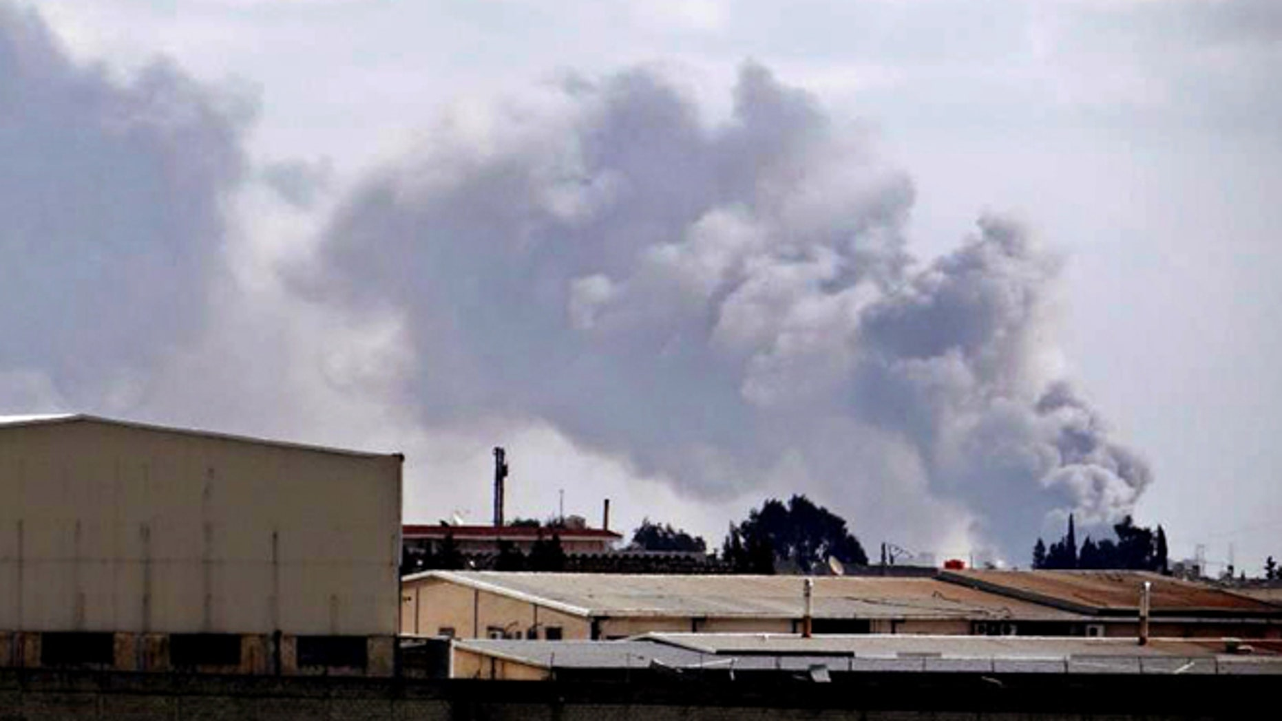 Feb. 12, 2013: Citizen journalism image provided by Aleppo Media Center AMC which has been authenticated based on its contents and other AP reporting, shows smoke rises from Aleppo International Airport, Syria.