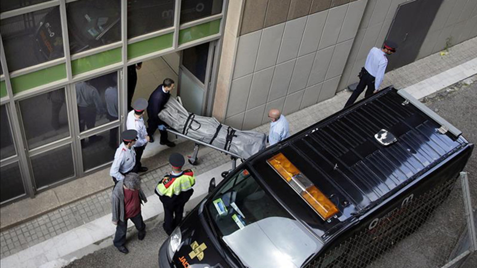 Coroner's office personnel remove the body of IES teacher Joan Fuster from the Barcelona school where a student opened fire on Monday, killing Fuster and injuring four others. (Photo: EFE)