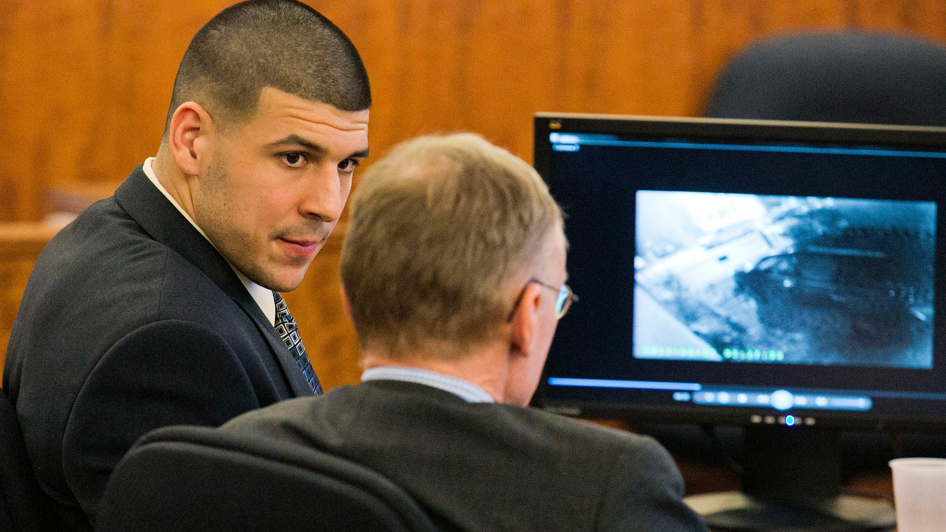 Former NFL player Aaron Hernandez looks at his attorney as security footage is seen on a monitor during his murder trial at the Bristol County Superior Court in Fall River, Mass.,  Friday, Feb. 20, 2015.  Grainy surveillance video shown to jurors in the murder trial of Hernandez on Friday shows the victim an hour before he was killed climbing into a car that prosecutors say was driven by Hernandez. (AP Photo/The Boston Herald, Dominick Reuter)