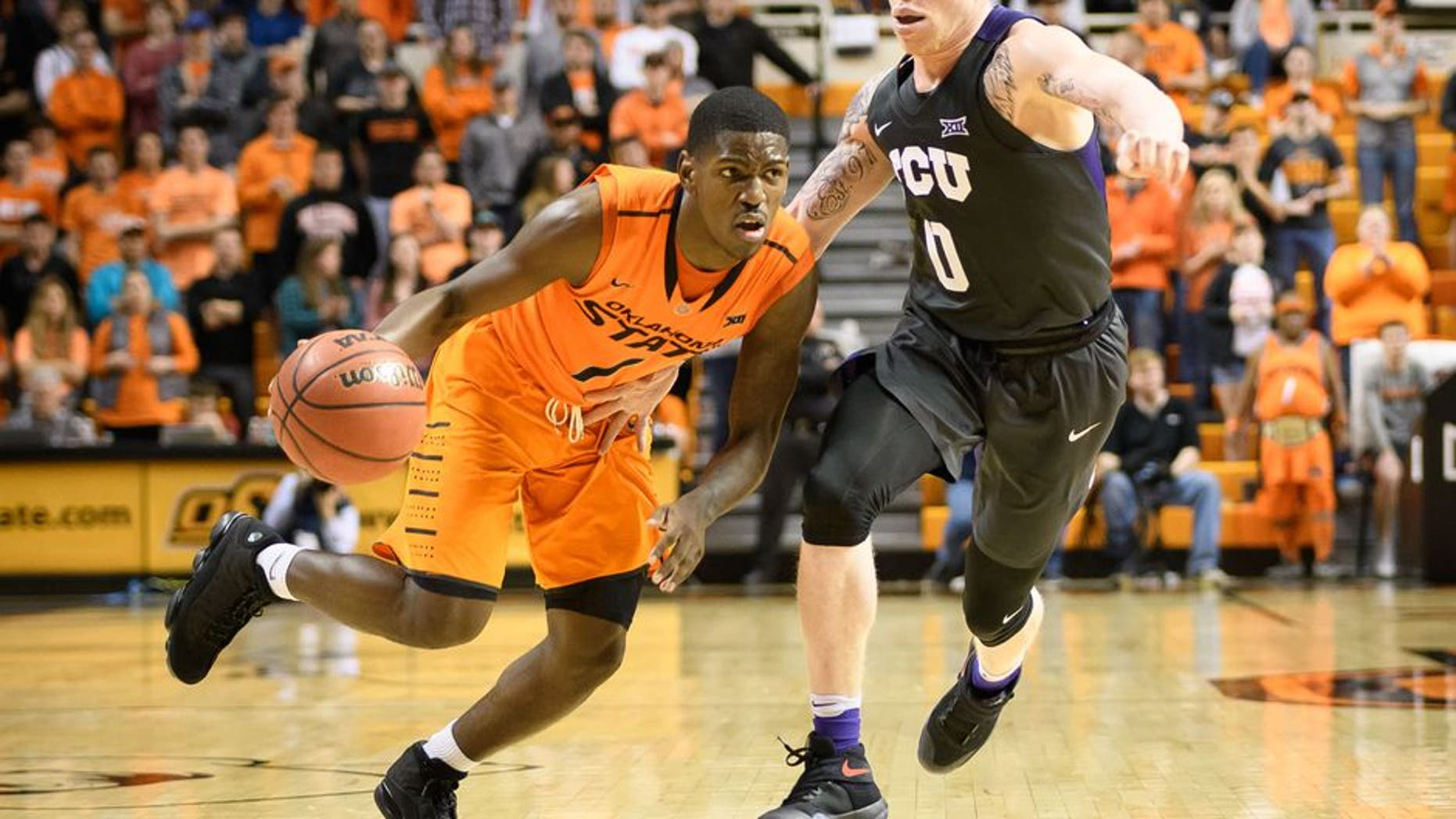 Jan 23, 2017; Stillwater, OK, USA; Oklahoma State Cowboys guard Jawun Evans (1) drives to the basket defended by TCU Horned Frogs guard Jaylen Fisher (0) during the second half at Gallagher-Iba Arena. Cowboys won 89-76. Mandatory Credit: Rob Ferguson-USA TODAY Sports