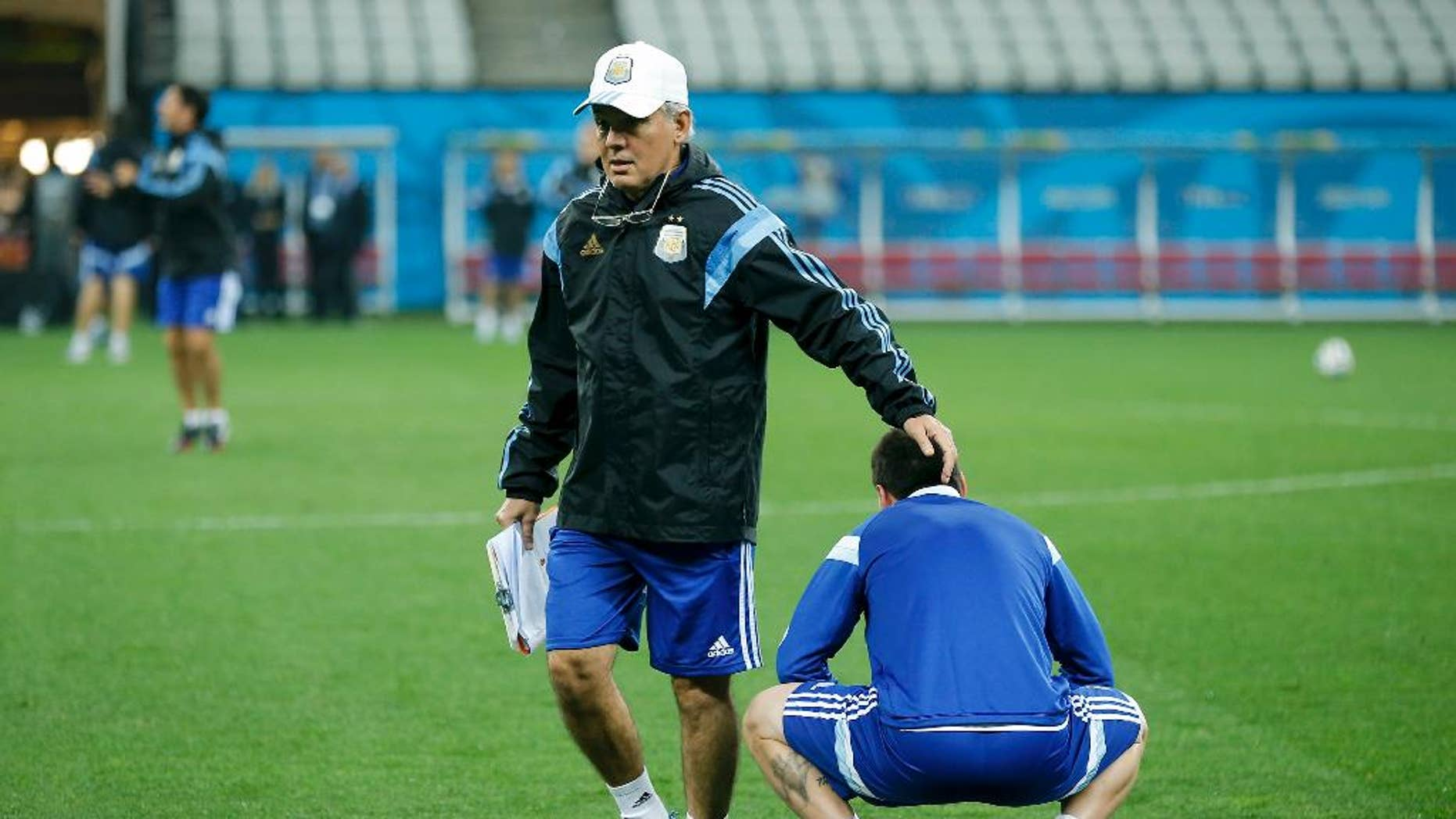 Argentina's head coach Alejandro Sabella touches the head of Argentina's Lionel Messi during a training session one day before their World Cup semifinal soccer match against Netherlands at Itaquerao Stadium in Sao Paulo, Brazil, Tuesday, July 8, 2014. (AP Photo/Victor R. Caivano)