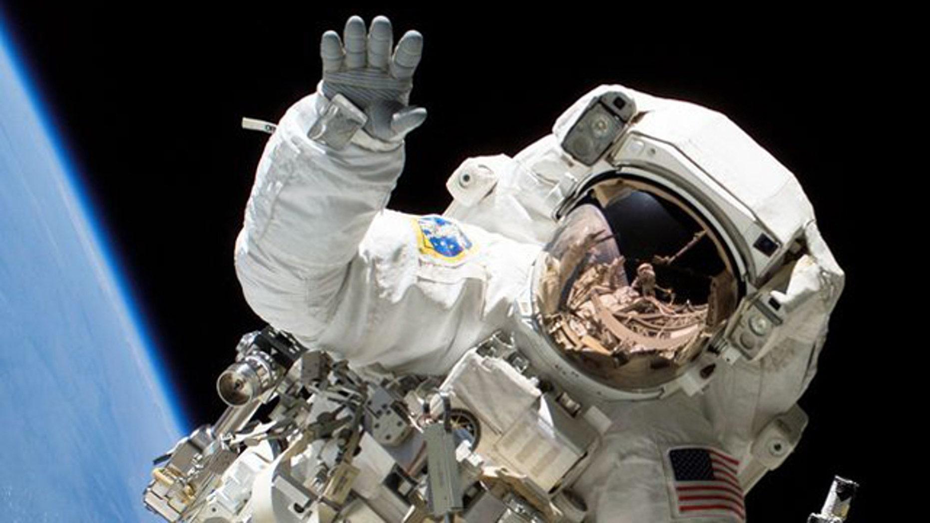 Astronaut Heidemarie M. Stefanyshyn-Piper waves at the camera during a spacewalk.