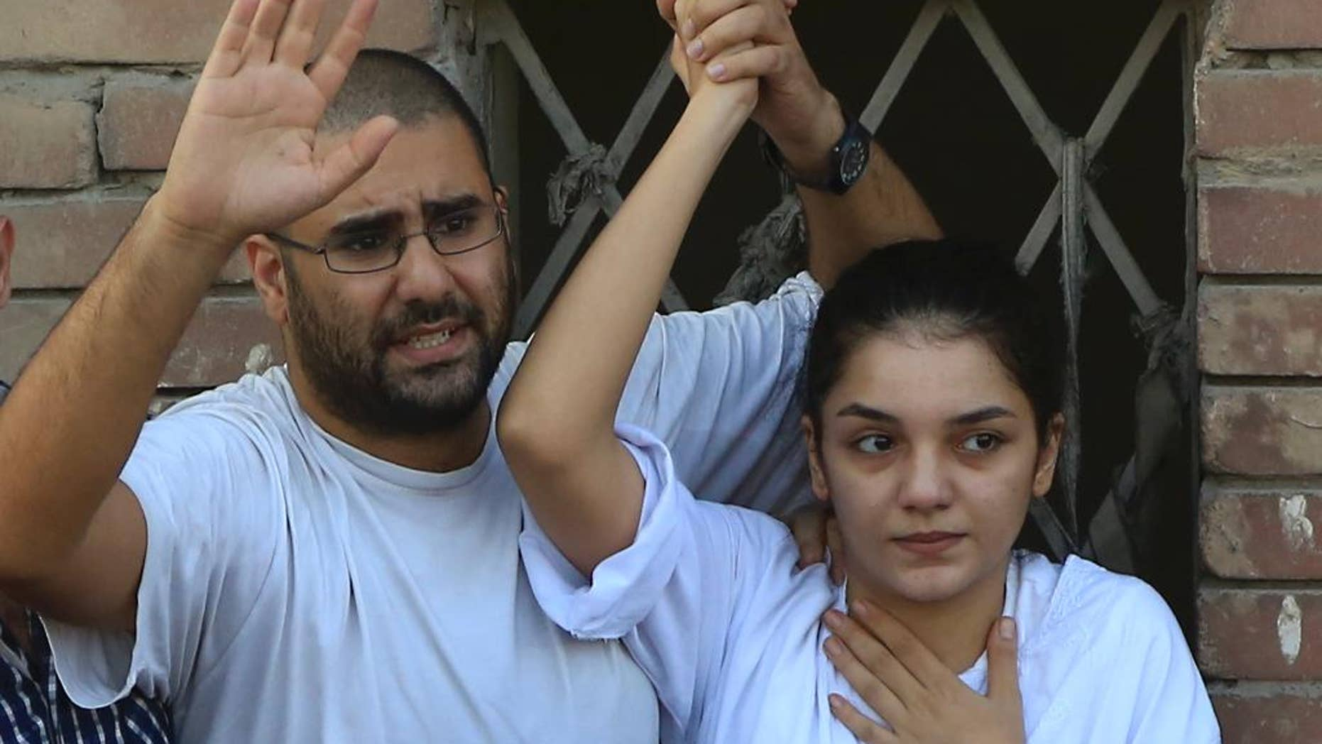 FILE - In this Thursday, Aug. 28, 2014 file photo prominent Egyptian blogger Alaa Abdel-Fattah, left, with his sister Sanaa Abdel-Fattah , speaks to the crowd after attending their father's funeral in Cairo, Egypt. Officials said the prominent activist voluntarily gave herself up to police on Saturday to start a six-month sentence passed against her last week for insulting the judiciary. (AP Photo/Hassan Ammar, File)