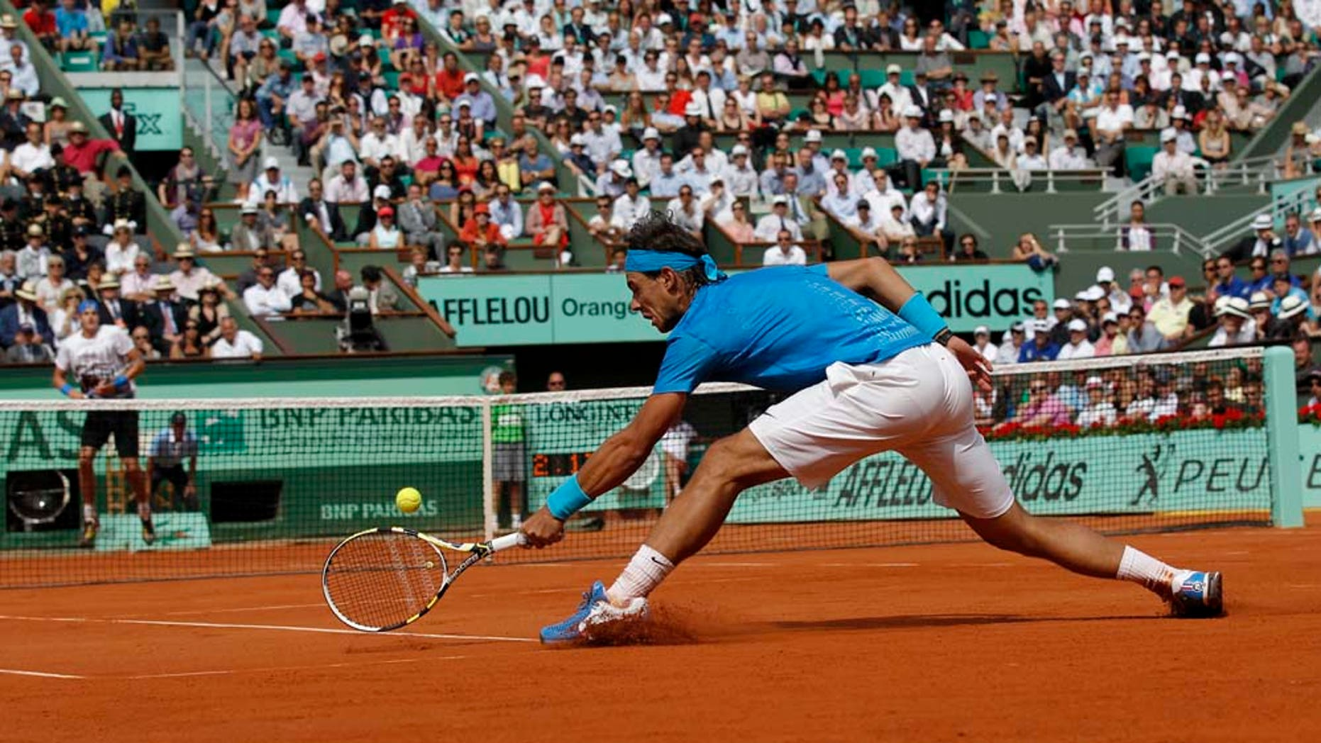 Defending champion Spain's Rafael Nadal returns the ball to USA's John Isner during their first round match of the French Open tennis tournament, at  the Roland Garros stadium in Paris, Tuesday, May 24, 2011. (AP Photo/Christophe Ena)