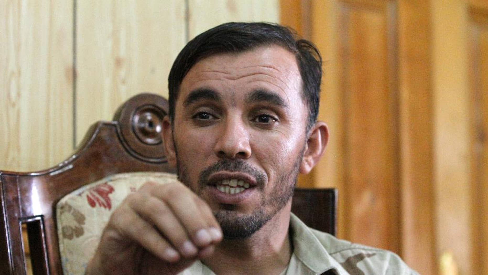In this Thursday, Aug. 4, 2016 photo, Gen. Abdul Raziq, Kandahar police chief, speaks during an interview with The Associated Press in Kandahar, Afghanistan. Raziq, regarded as one of the country's most powerful men has banned the use of the Pakistani currency in the key southern province of Kandahar. Raziq's ban came into effect last week. Traders said it had an immediate effect, with the afghani strengthening in recent days. (AP Photos/Allauddin Khan)