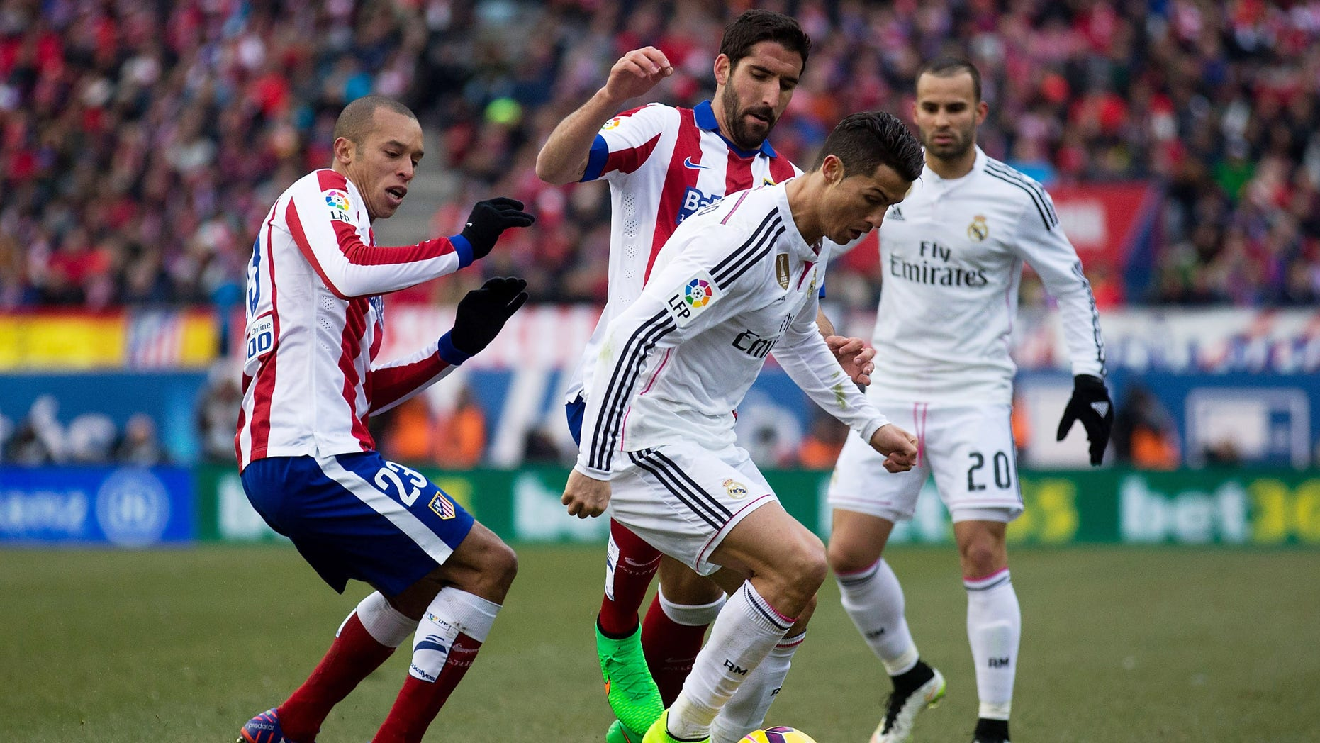 MADRID, SPAIN - FEBRUARY 07: Cristiano Ronaldo (R) of Real Madrid CF competes for the ball with Raul Garcia (2ndL) of Atletico de Madrid and his teammate Joao Miranda (L) during the La Liga match between Club Atletico de Madrid and Real Madrid CF at Vicente Calderon Stadium on February 7, 2015 in Madrid, Spain.  (Photo by Gonzalo Arroyo Moreno/Getty Images)