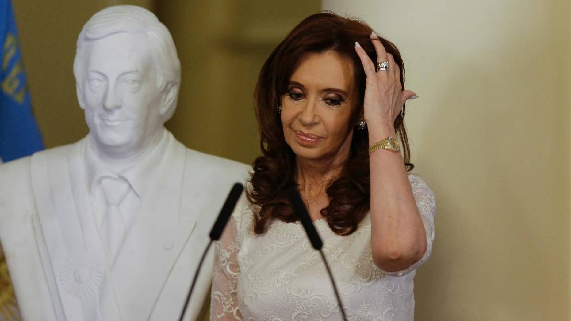 FILE - In this Dec. 9, 2015 file photo, Argentina's President Cristina Fernandez pushes her hair back after unveiling a bust of her late husband, and former president, Nestor Kirchner, at the presidential palace in Buenos Aires, Argentina. An Argentine judge indicted Fernandez on Tuesday, Dec. 27, 2016, in a corruption case involving public works. (AP Photo/Ricardo Mazalan, File)