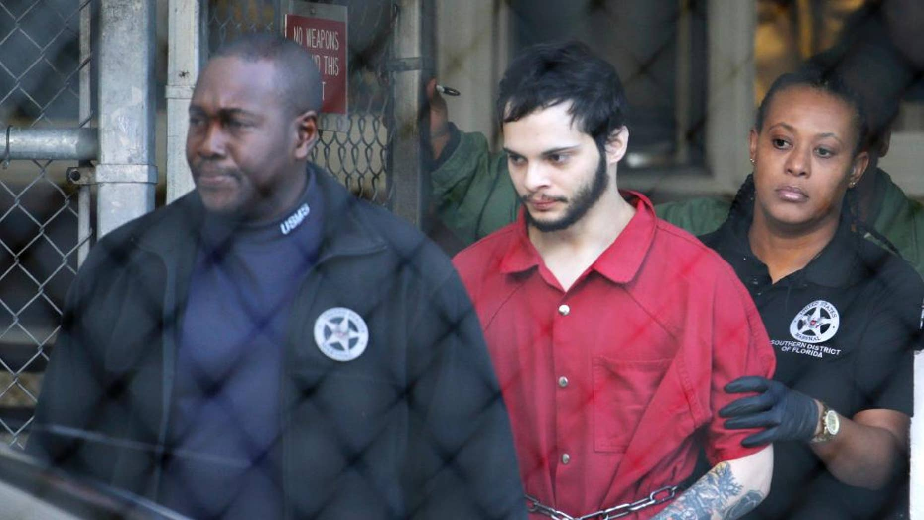 FILE- In this Jan. 30, 2017, file photo, Esteban Santiago, center, is led from the Broward County jail for an arraignment in federal court in Fort Lauderdale, Fla. Prosecutors and defense attorneys for Santiago said at a hearing Wednesday, March 15, 2017, the death penalty decision process has just begun. Santiago is accused in the Jan. 6 shooting that killed five and wounded six at Fort Lauderdale-Hollywood International Airport. (AP Photo/Lynne Sladky, File)