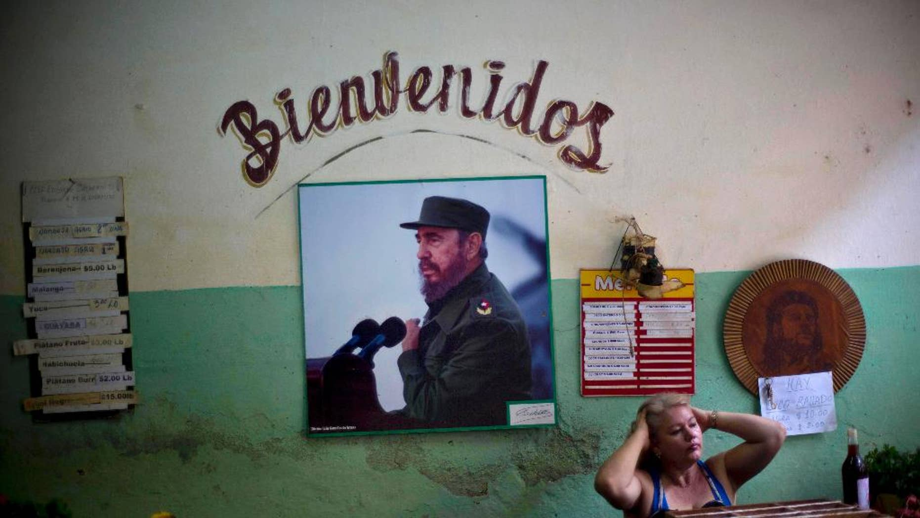 """FILE - In this Dec. 26, 2014 file photo, a photograph of Fidel Castro hangs under the Spanish word """"Welcome"""" on the wall at a state-run food market in Havana, Cuba. On Monday, Jan. 26, 2015, after more than a month of silence, Castro made his first public comments about the news that the U.S. and his island nation will restore diplomatic relations after more than 50 years of hostility. (AP Photo/Ramon Espinosa, File)"""