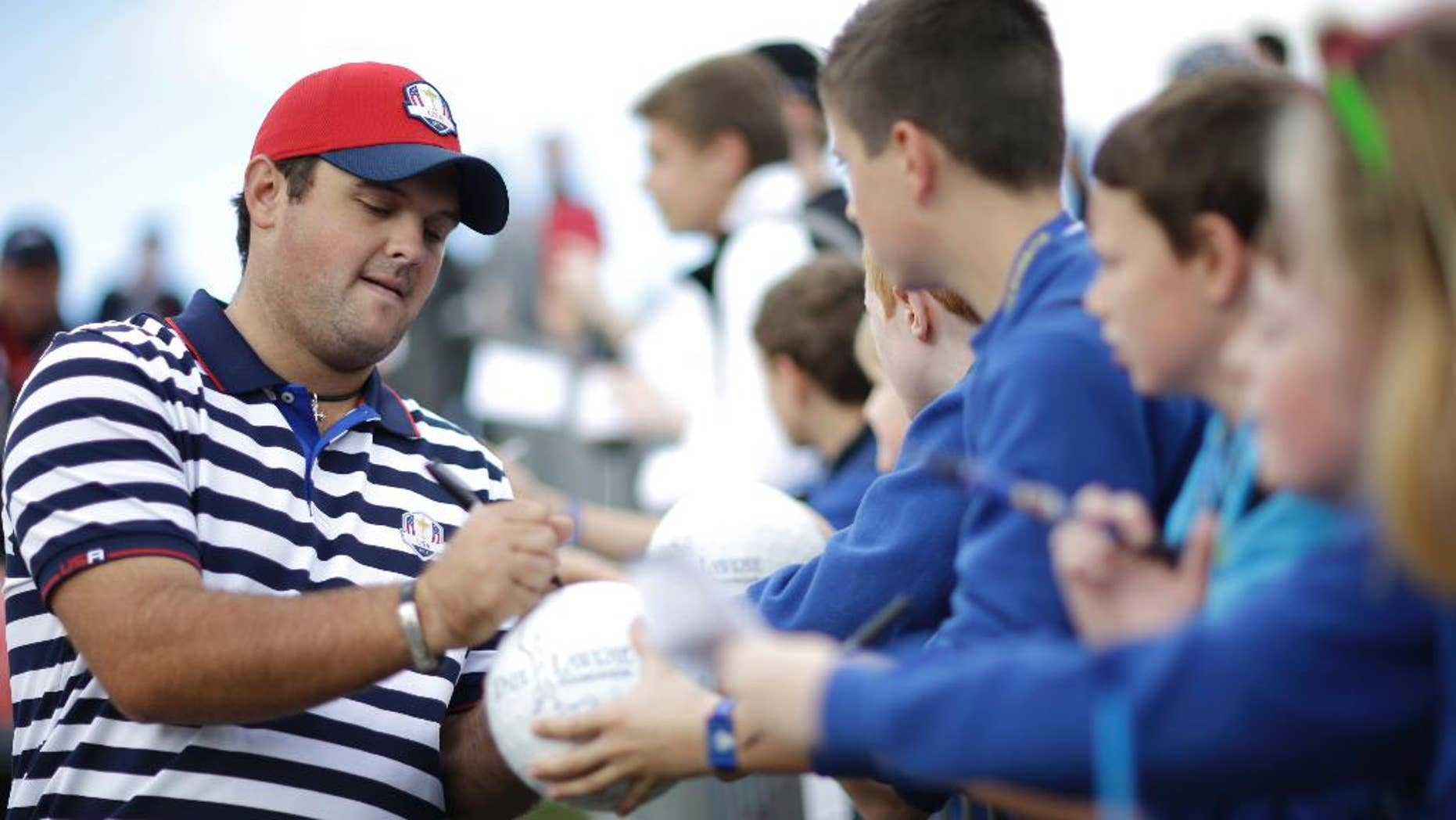 Patrick Reed of the US signs autographs for fans on his way to the 9th tee box during a practice round ahead of the Ryder Cup golf tournament, at Gleneagles, Scotland, Wednesday, Sept. 24, 2014. (AP Photo/Matt Dunham)