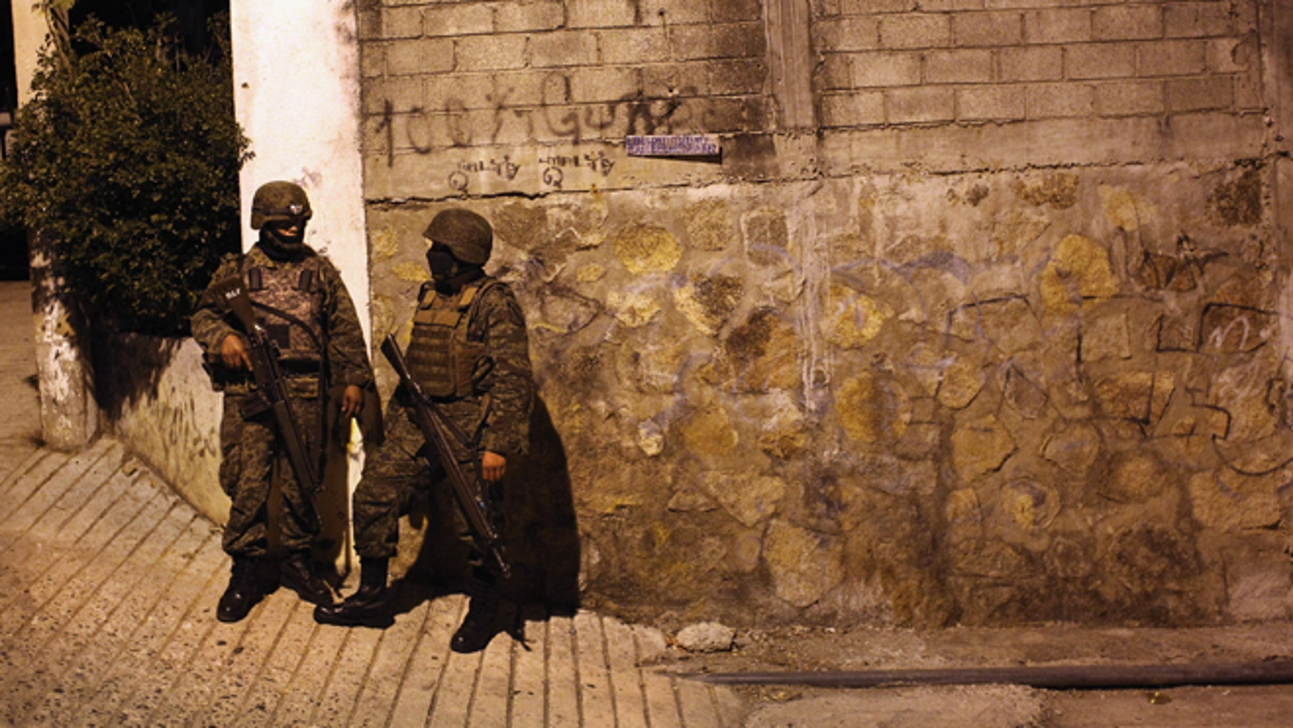 ACAPULCO, MEXICO - MARCH 03:  Mexican army soldiers stand guard near a suspected drug-related murder site  March 3, 2012 in Acapulco, Mexico. A forensics team excavated five corpses from the floor of an abandoned house. Officials said the five victims were apparently buried alive in concrete. Drug violence has surged in the coastal resort in the last year, making Acapulco the second most deadly city in Mexico after Juarez. One of Mexico's top tourist destinations, Acapulco has suffered a drop in business, especially from foreign tourists, due to the violence. Toursim accounts for about 70 percent of the economy of Acapulco's state of Guerrero and 9 percent of Mexico's economy.  (Photo by John Moore/Getty Images)
