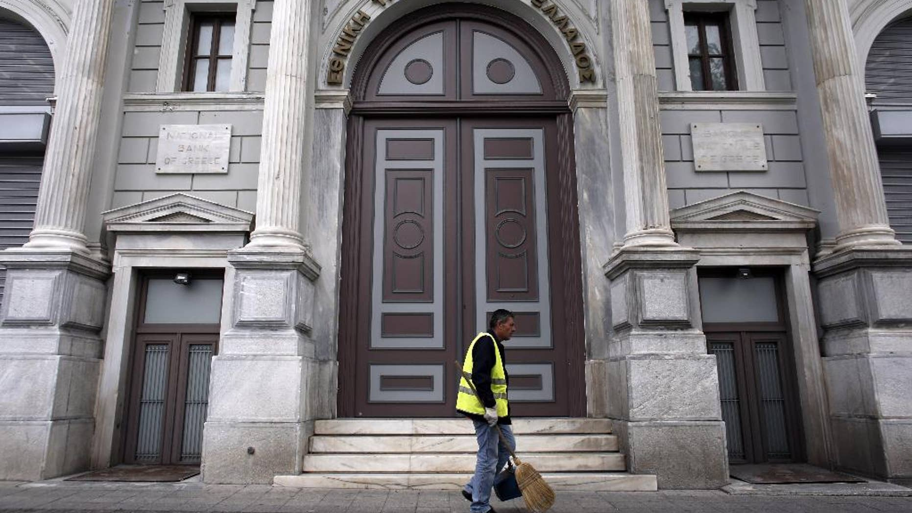 A cleaning worker walks past the headquarters of National Bank of Greece, in Athens, on Sunday, Oct. 26, 2014. The European Central Bank says 13 of Europe's 130 biggest banks have flunked an in-depth review of their finances and must increase their capital buffers against losses by 10 billion euros ($12.5 billion). The ECB said 25 banks in all were found to need stronger buffers — but that 12 have already made up their shortfall. The remaining 13 now have two weeks to tell the ECB how they plan to increase their capital buffers. (AP Photo/Kostas Tsironis)
