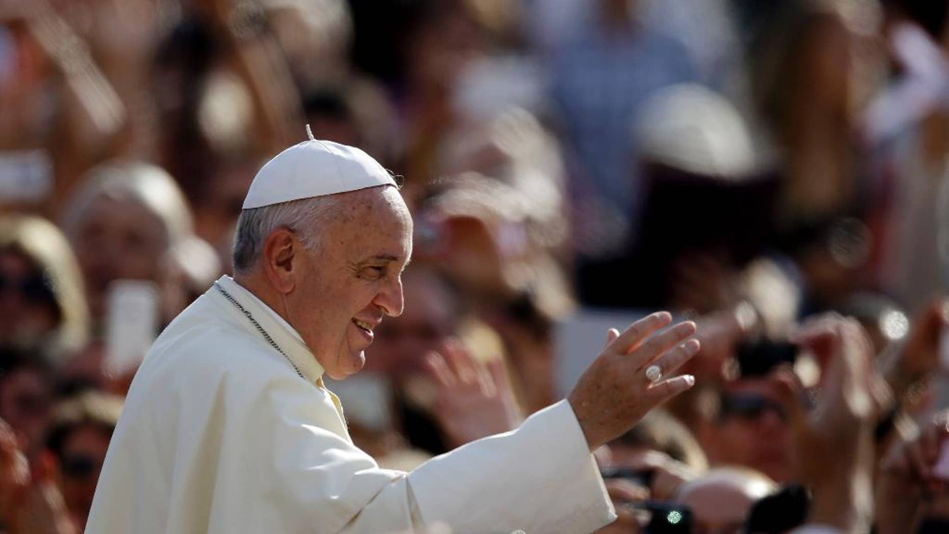 Pope Francis blesses faithful upon his arrival for the weekly general audience in St. Peter's Square at the Vatican, Wednesday, Oct. 1, 2014. (AP Photo/Gregorio Borgia)