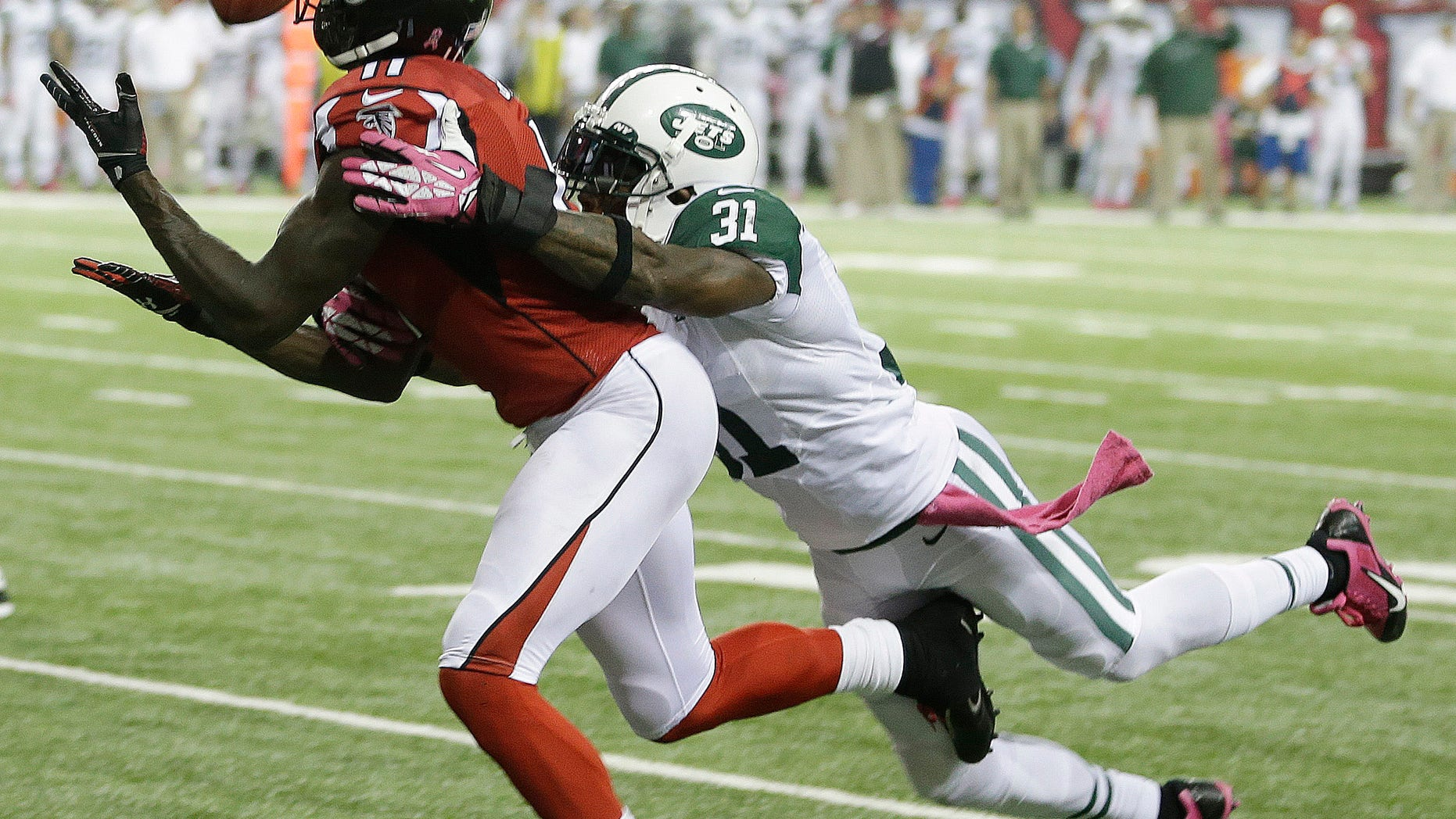 Atlanta Falcons wide receiver Julio Jones (11) misses a catch as New York Jets cornerback Antonio Cromartie (31) defends during the second half of an NFL football game, Monday, Oct. 7, 2013, in Atlanta. (AP Photo/John Bazemore)