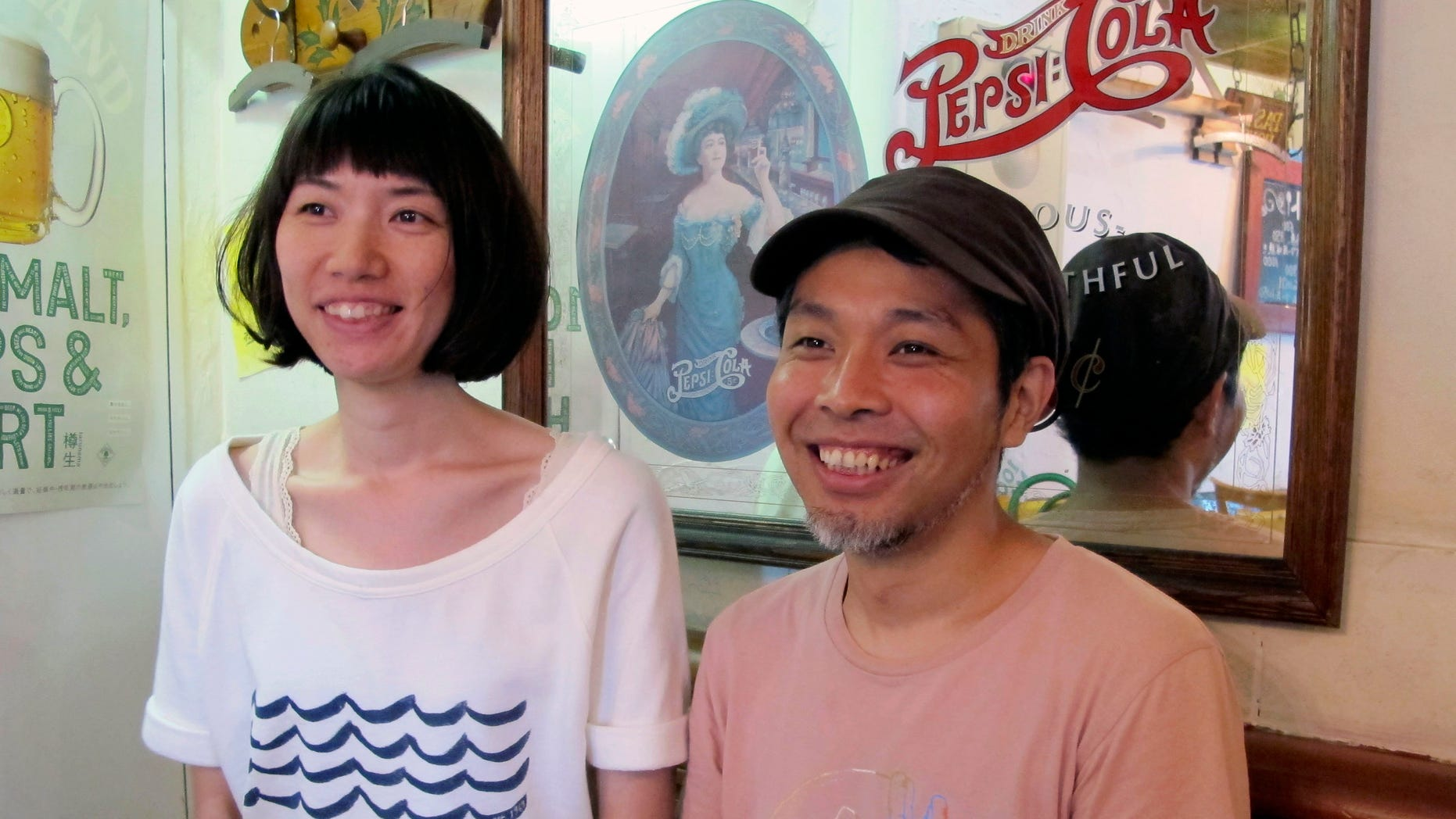 In this Friday, July 12, 2013, photo, Teruyuki Kawabata, right, 36, and his wife Haruna, 32, smile during an interview in Tokyo. Both Teruyuki and Haruna were children when Japan's bubble economy burst more than two decades ago. Now, they have little interest in the stock market.  (AP Photo/Yuri Kageyama)