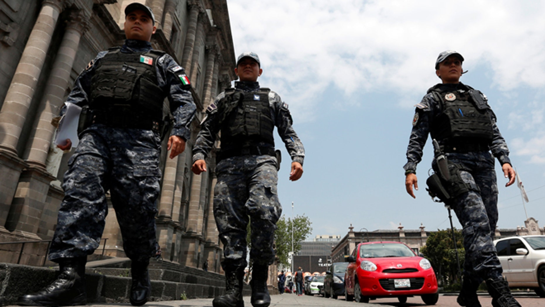 FILE: Police officers walk on the main square a day after local election in Toluca, Mexico.