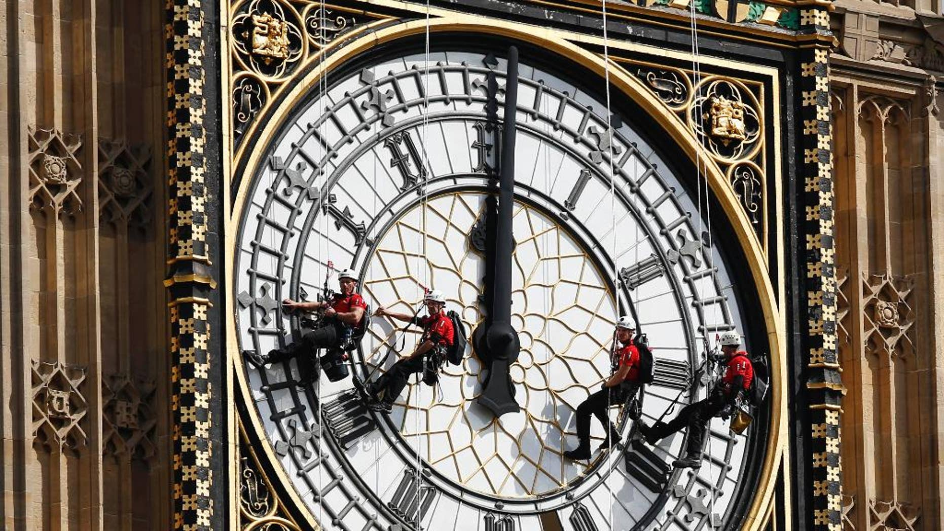 FILE- In this file photo dated  Monday, Aug. 18, 2014, workers abseil outside the clock face as they clean Big Ben's clock tower of the Houses of Parliament in London.  According to reports published Sunday Oct. 18, 2015, the chimes of Big Ben may fall silent for many months as urgent repairs are carried out to the clock and the tower, which  must begin as soon as possible.(AP Photo/Sang Tan, FILE)