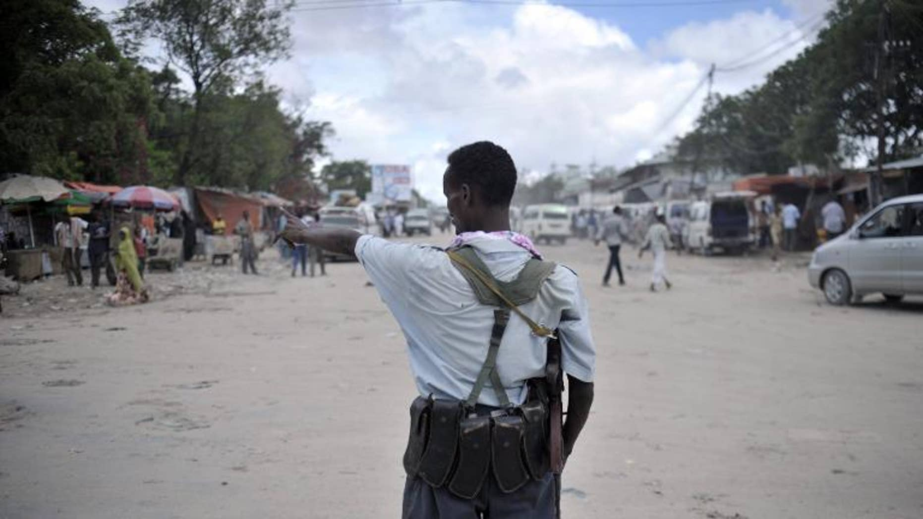 An AU-UN IST picture shows a Somali policeman directing traffic at a checkpoint in downtown Mogadishu, May 3, 2013.