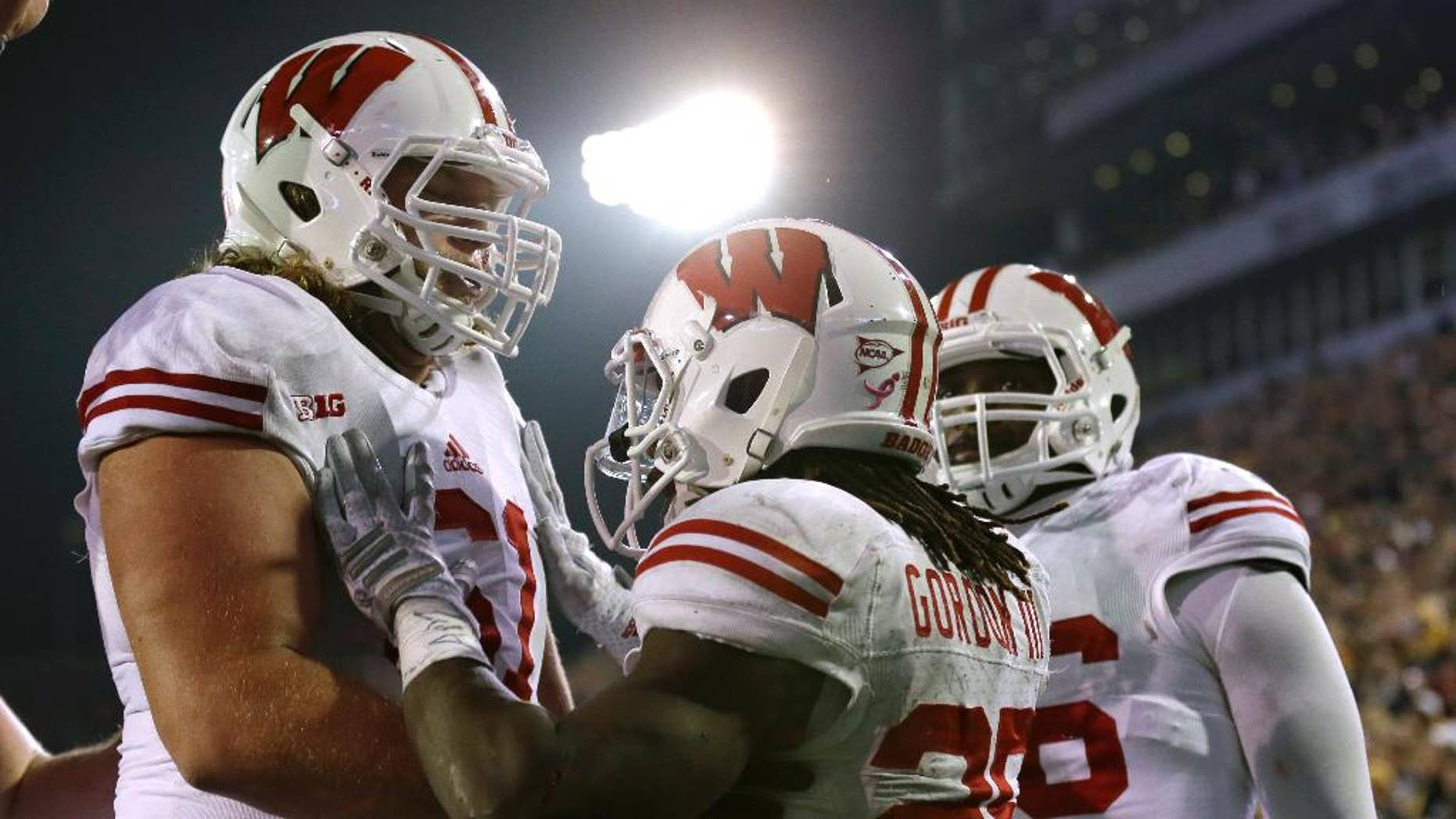 Wisconsin running back Melvin Gordon, center, celebrates with teammates after scoring on a 23-yard touchdown run in the second half of an NCAA college football game against Iowa, Saturday, Nov. 22, 2014, in Iowa City, Iowa. Wisconsin won 26-24. (AP Photo/Charlie Neibergall)