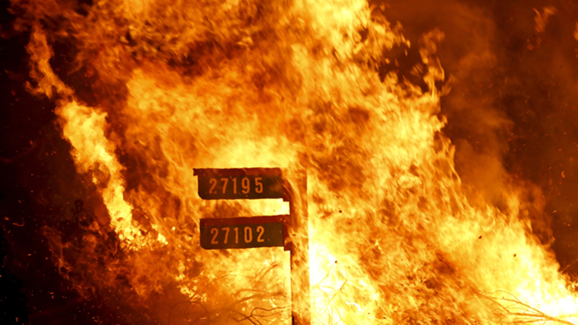 Flames consume a sign containing addresses to homes along Morgan Valley Road in Lake County, California, in this August 12, 2015 file photo. (Photo: REUTERS/Robert Galbraith/Files)