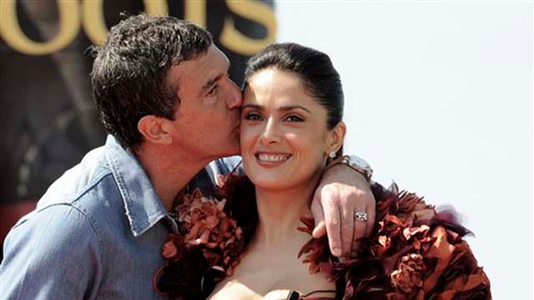 Actor Antonio Banderas, left, kisses actress Salma Hayek on the cheek during a photo call for Puss in Boots, at the 64th international film festival, in Cannes, southern France, Wednesday, May 11, 2011. (AP Photo/Jonathan Short)