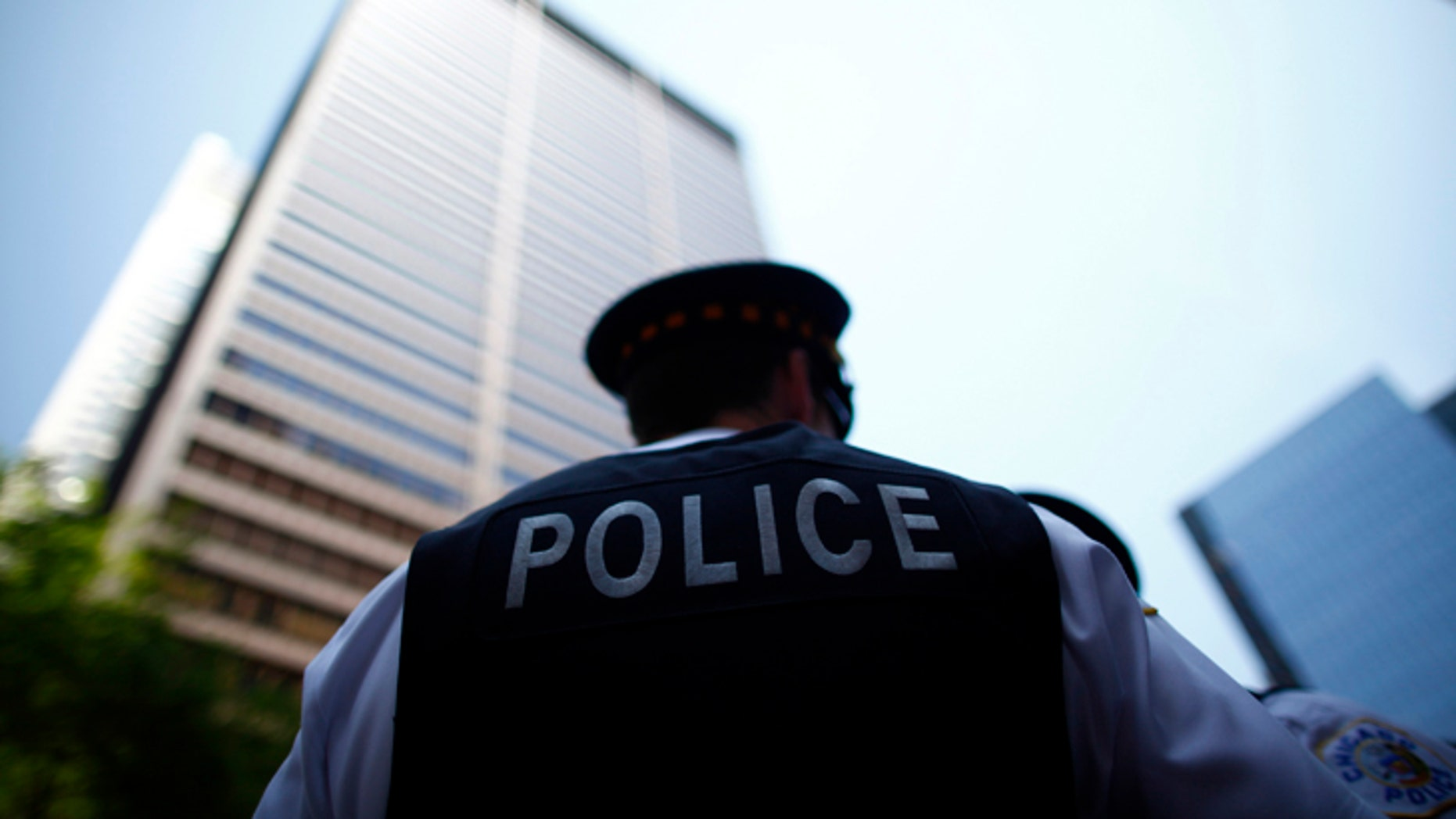 File photo - Police officers watch as protesters rally during a demonstration leading up to the NATO Summit in Chicago May 18, 2012. (REUTERS/Eric Thayer)