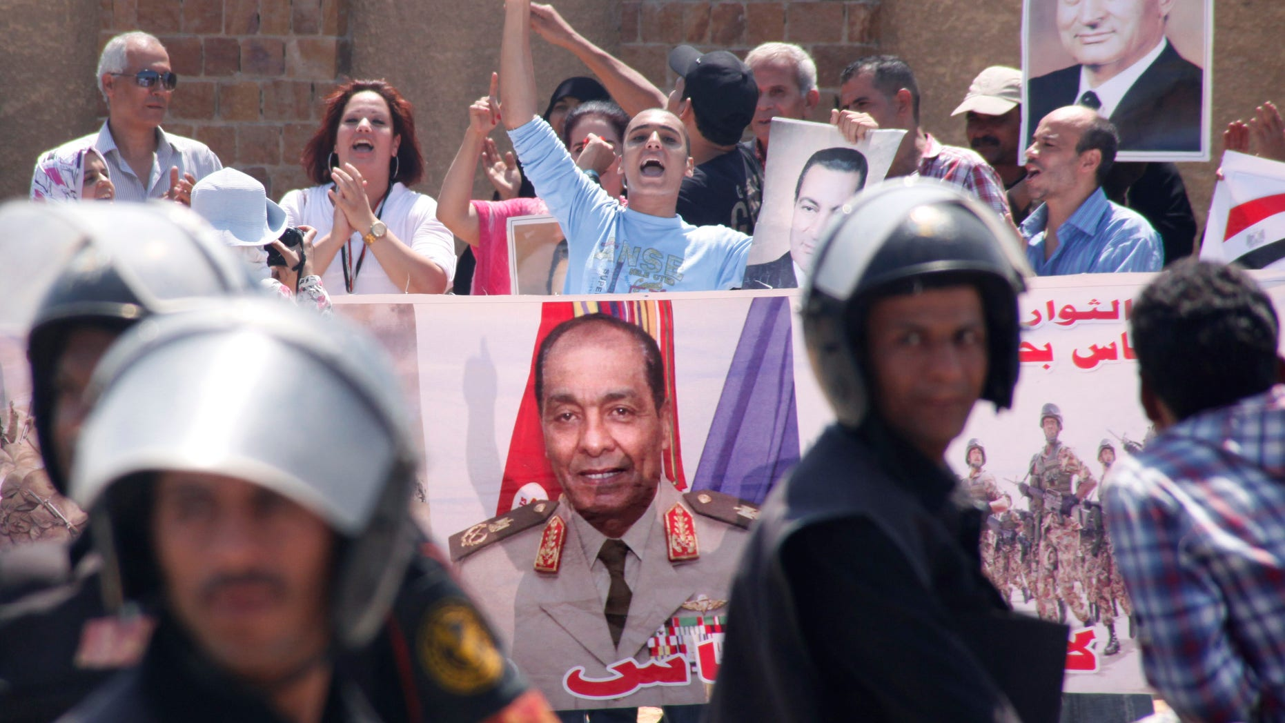 Egyptian pro-Mubarak supporters flash his posters and a giant poster showing field Marshal Mohammed Hussein Tantawi, at center, outside police academy court in Cairo, Egypt, Sunday, Sept.11, 2011 where Mubarak, his two sons Alaa and Gamal, his security chief Habib el-Adly and six top police officers face a session of trial, on charges they ordered the use of lethal force against protesters during Egypt's 18-day uprising killing 850 protesters were killed. Tantawi, Egypt's military ruler Tantawi and one-time confidant of Hosni Mubarak, has failed to attend a court session in which he was expected to offer highly anticipated testimony about the former president's alleged role in the death of protesters.