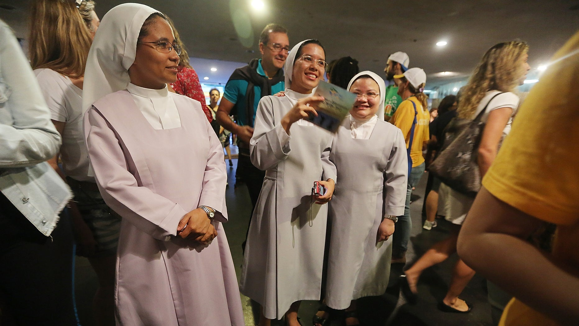 RIO DE JANEIRO, BRAZIL - JULY 21: Nuns stand outside a mass in the Arpoador neighborhood on July 21, 2013 in Rio de Janeiro, Brazil. More than 1.5 million pilgrims are expected to join Pope Francis for his visit to the Catholic Church's World Youth Day celebrations. Pope Francis is scheduled to visit Brazil from July 22 to 28.  (Photo by Mario Tama/Getty Images)