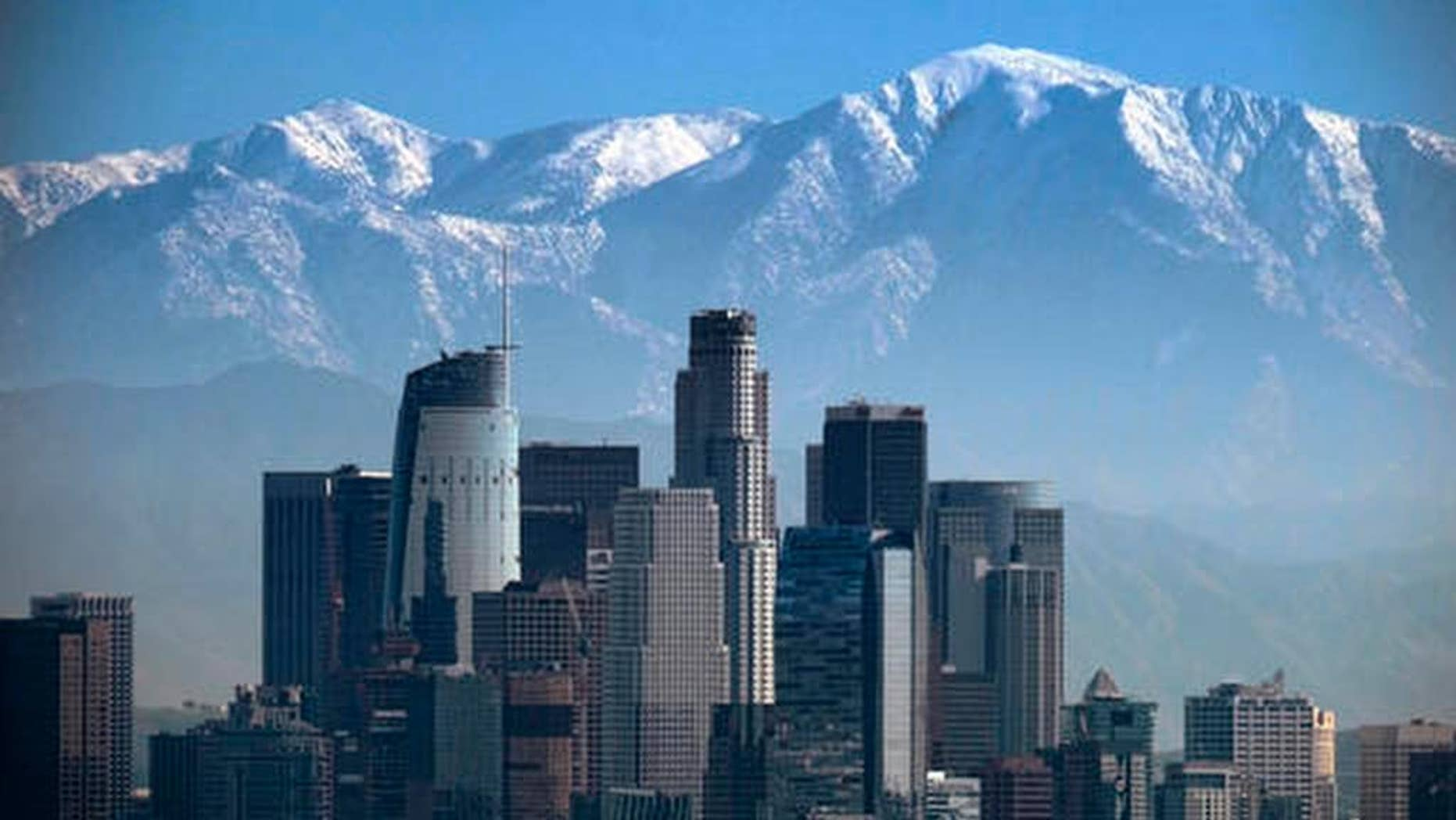 """FILE - This Jan. 25, 2017 file photo shows a snow covered Mount Baldy, the highest peak among the San Gabriel Mountains behind downtown Los Angeles. Searchers have found the body of a veteran hiker who vanished while climbing the 10,000-foot (3,000-meter) mountain just northeast of Los Angeles. Seuk """"Sam"""" Kim, had hiked to the top of Mount Baldy in the San Gabriel Mountains more than 700 times before he went missing last week. (AP Photo/Richard Vogel, File)"""