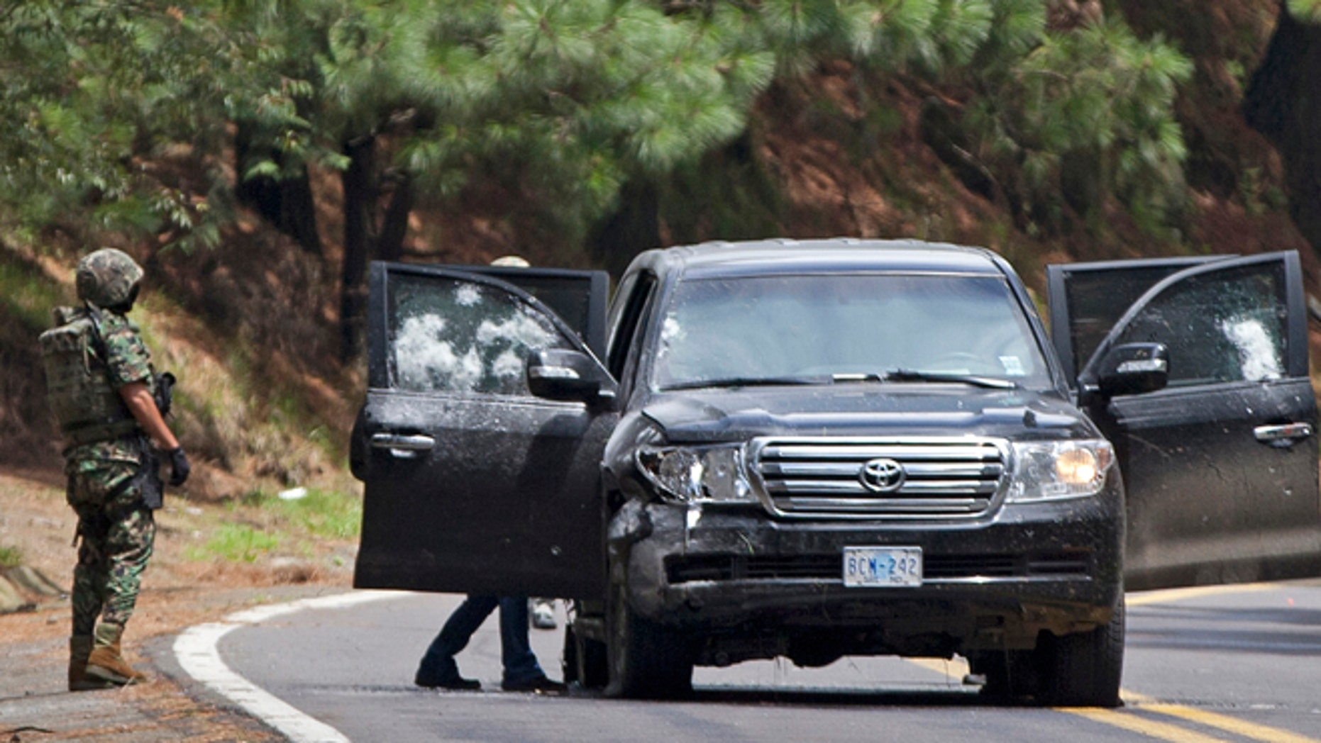 An armored U.S. Embassy vehicle is checked by military personal after it was attacked near Tres Marias, Mexico, in August. (AP)