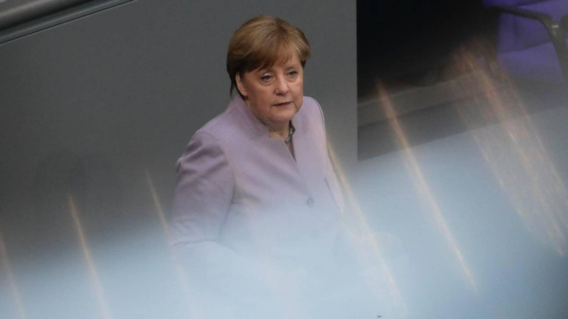 In this photo taken with reflections of a hand rail at the visitors tribune, German Chancellor Angela Merkel delivers her speech about the European Union at the German parliament Bundestag in Berlin, Thursday, April 27, 2017. (AP Photo/Markus Schreiber)