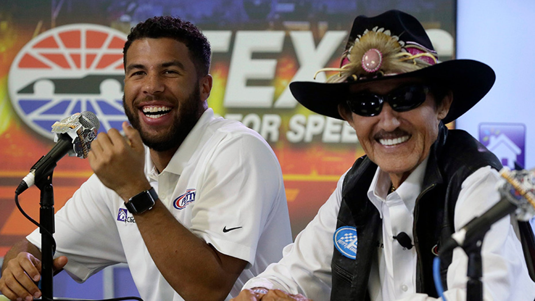 Darrell Wallace Jr., left,  laughs with Richard Petty during news conference before NASCAR Cup series auto race qualifying at Texas Motor Speedway in Fort Worth, Texas, Friday, Nov. 3, 2017. Richard Petty Motorsports announced that Wallace Jr. will drive the No. 43 car for the organization beginning in 2018. (AP Photo/LM Otero)