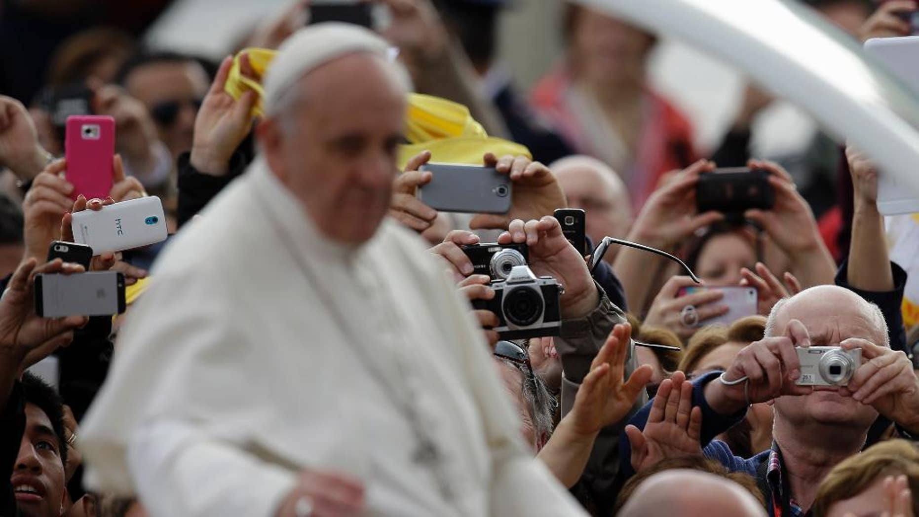 Faithful take pictures of Pope Francis touring St.Peter's Square aboard of his pope-mobile  as he arrives for his general audience at the Vatican, Wednesday, April 9, 2014. (AP Photo/Gregorio Borgia)