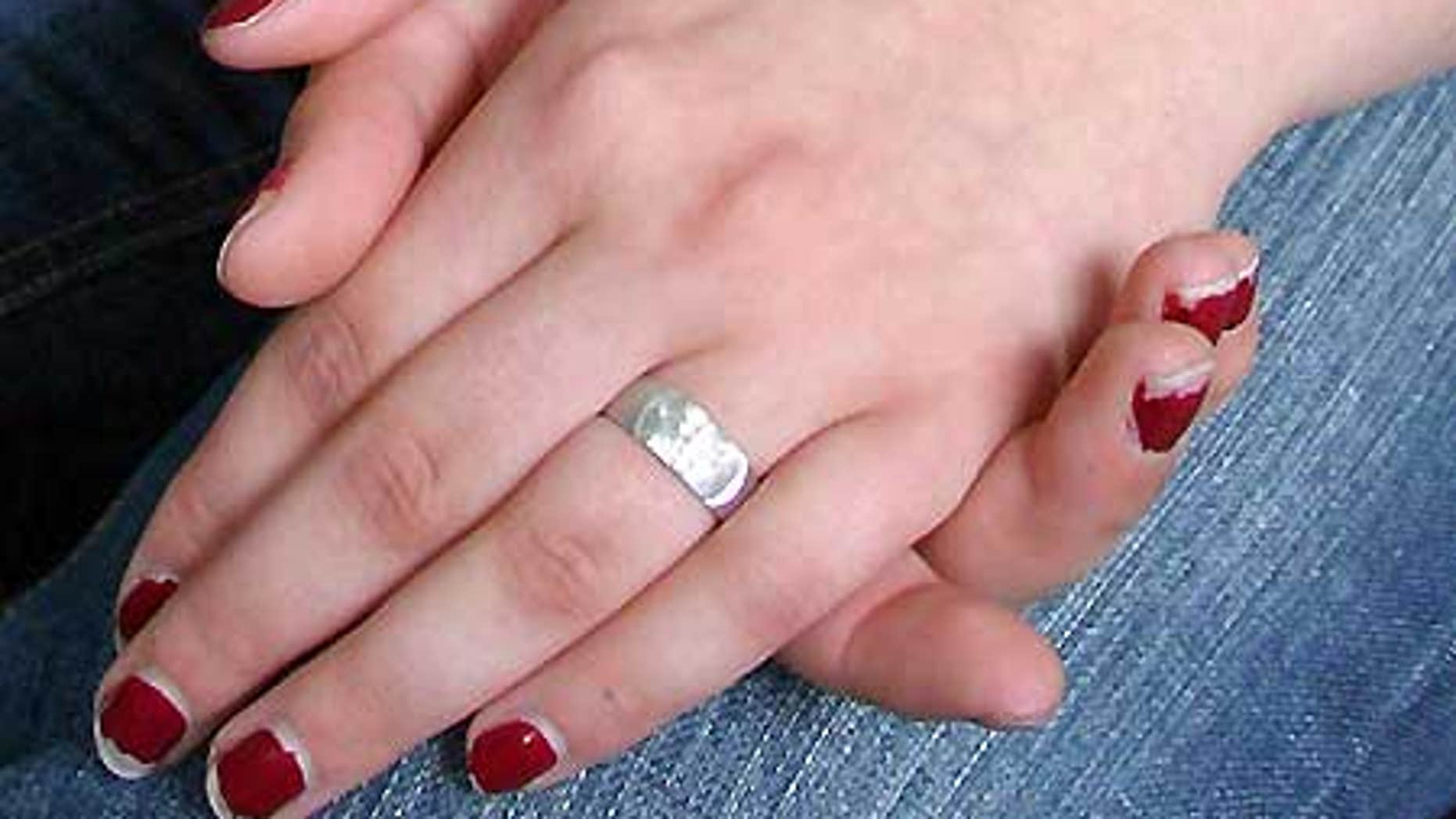 A teenaged girl wears a purity ring representing her pledge to remain celibate until marriage.
