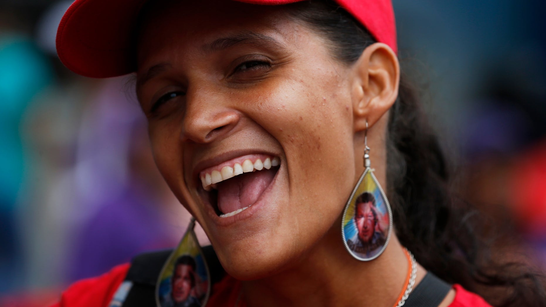 A woman wearing earrings designed with an image of the late President Hugo Chavez, smiles during a pro-government rally in Caracas, Venezuela, Saturday, Feb. 22, 2014. Venezuelans on both sides of the nation's political divide took to the streets on Saturday after nearly two weeks of mass protests that have Venezuelan President Nicolas Maduro scrambling to reassert his leadership. (AP Photo/Fernando Llano)