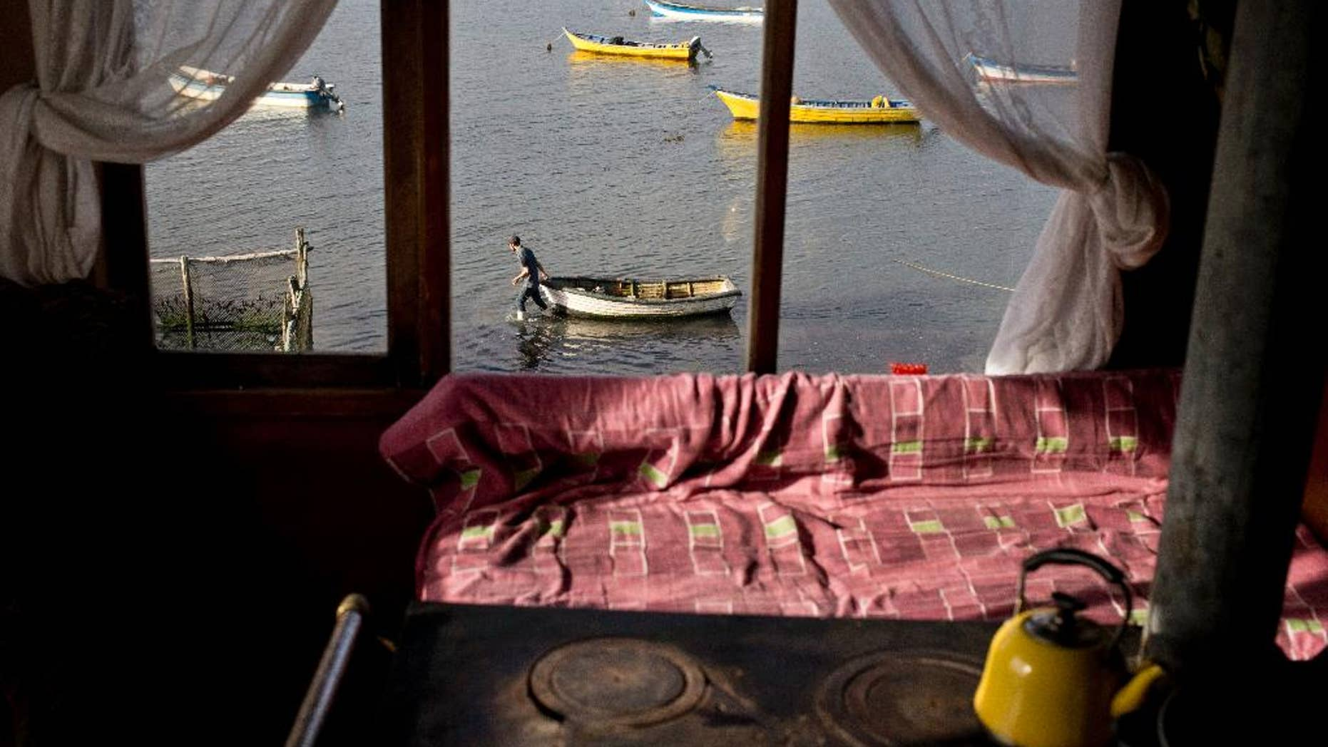 """In this May 10, 2016, Marco, the 19-year-old son of fisherwoman Marisol Millaquien prepares to take out a boat on an expedition, in hopes of providing food for the dinner table, in Quetalmahue, on Chile's Chiloe Island, during the country's worst ever """"red tide"""" environmental disaster. The view from Millaquien's stilt home is desolate: dozens of abandoned ghostly boats, dead birds and shellfish. """"I'm 46. I've seen red tide before, but never like this,"""" she said. (AP Photo/Esteban Felix)"""