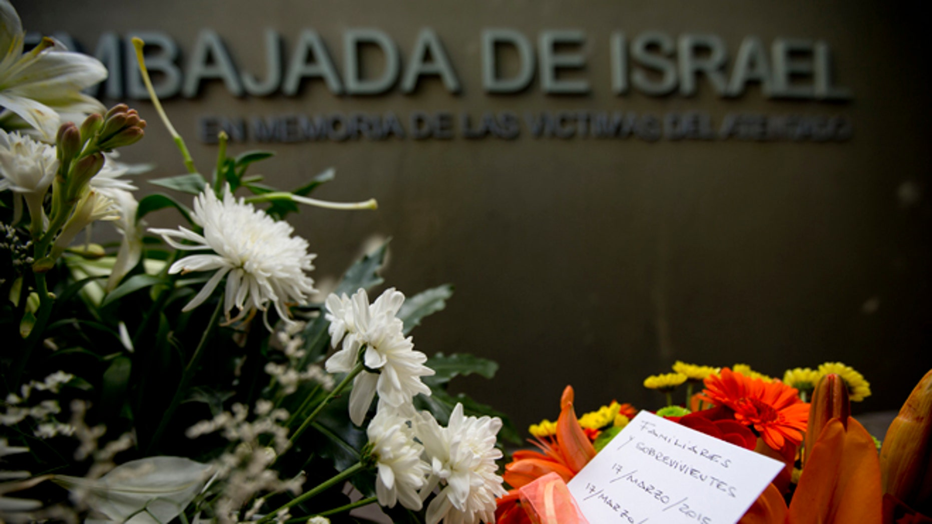"""A piece of paper reading in Spanish """"Relatives and survivors, March 17, 2015, March 17, 1992"""" is placed on floral arrangements that sit where the Israeli Embassy used to be, during an act to commemorate the 23rd anniversary of the bomb attack that destroyed the Israeli Embassy building killing 22 people in Buenos Aires, Argentina, Tuesday, March 17, 2015. (AP Photo/Natacha Pisarenko)"""