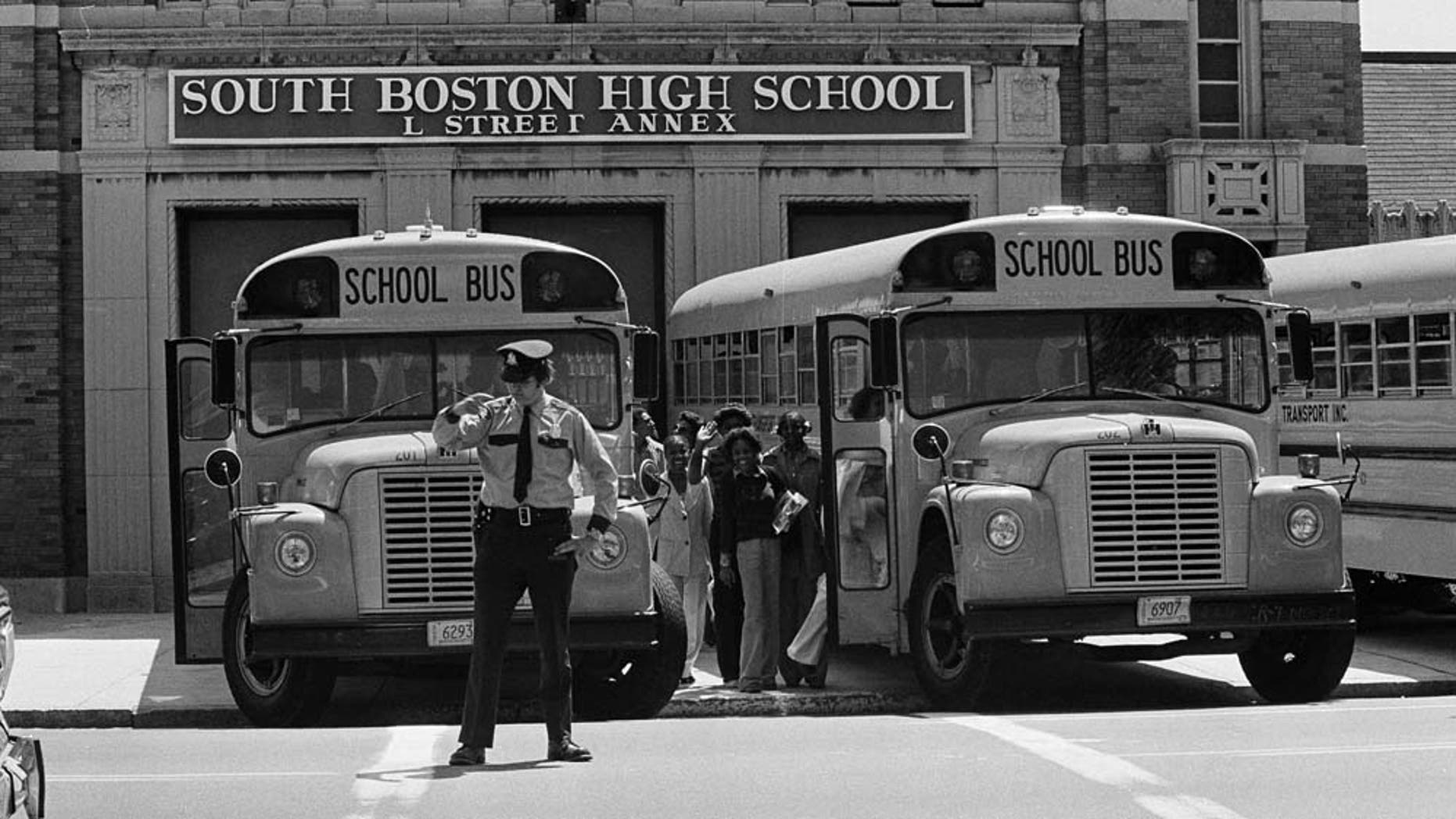 FILE - In this May 30, 1975 file photo black students attending South Boston High School climb into buses backed up close to the school's doors that will take them home after classes. In front stands one of the policemen who have been needed to keep the peace at Boston schools since September when the city started a court-ordered school integration program requiring the busing of 18 percent of public school students. (AP Photo/J. Walter Green)