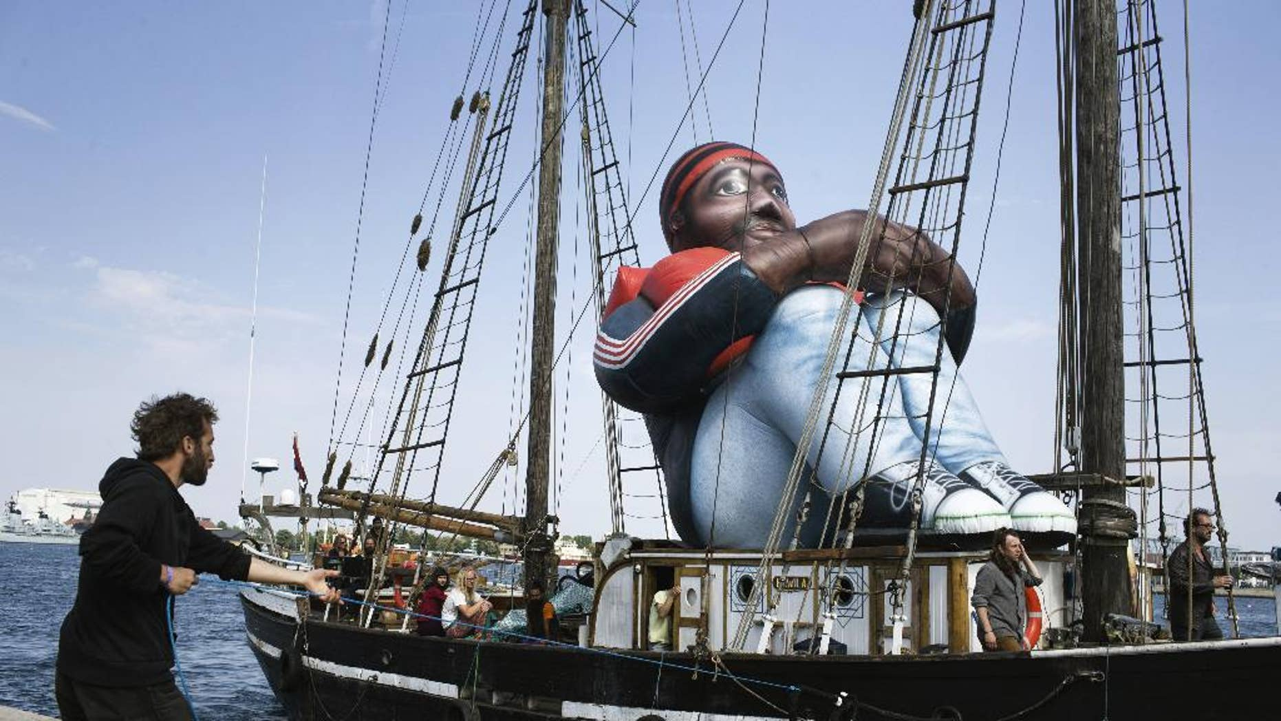 """The artwork """"Inflatable Refugee"""" by Belgian artist collective Shellekens and Peleman on the deck of a wooden boat arrives in Copenhagen, Monday May 23, 2016. The creators say the artwork is a """"symbol of the dehumanization of the refugee and the current refugee crisis happening in the world."""" (Mathias Svold Maagaard/Polfoto via AP)  DENMARK OUT"""