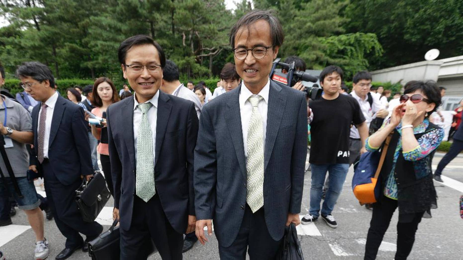 South Korean human right lawyers leave after a court hearing on the detention of North Korean defectors as an anti-North Korean protester, right, shouts to them in front of the Seoul District Court in Seoul, South Korea, Tuesday, June 21, 2016. As South Korea's main spy agency prepares a courtroom defense of its continued detention of 12 North Korean waitresses it says fled from China, Pyongyang is using the women's relatives and colleagues to step up its accusations that they were tricked into leaving their jobs and essentially kidnapped.(AP Photo/Ahn Young-joon)