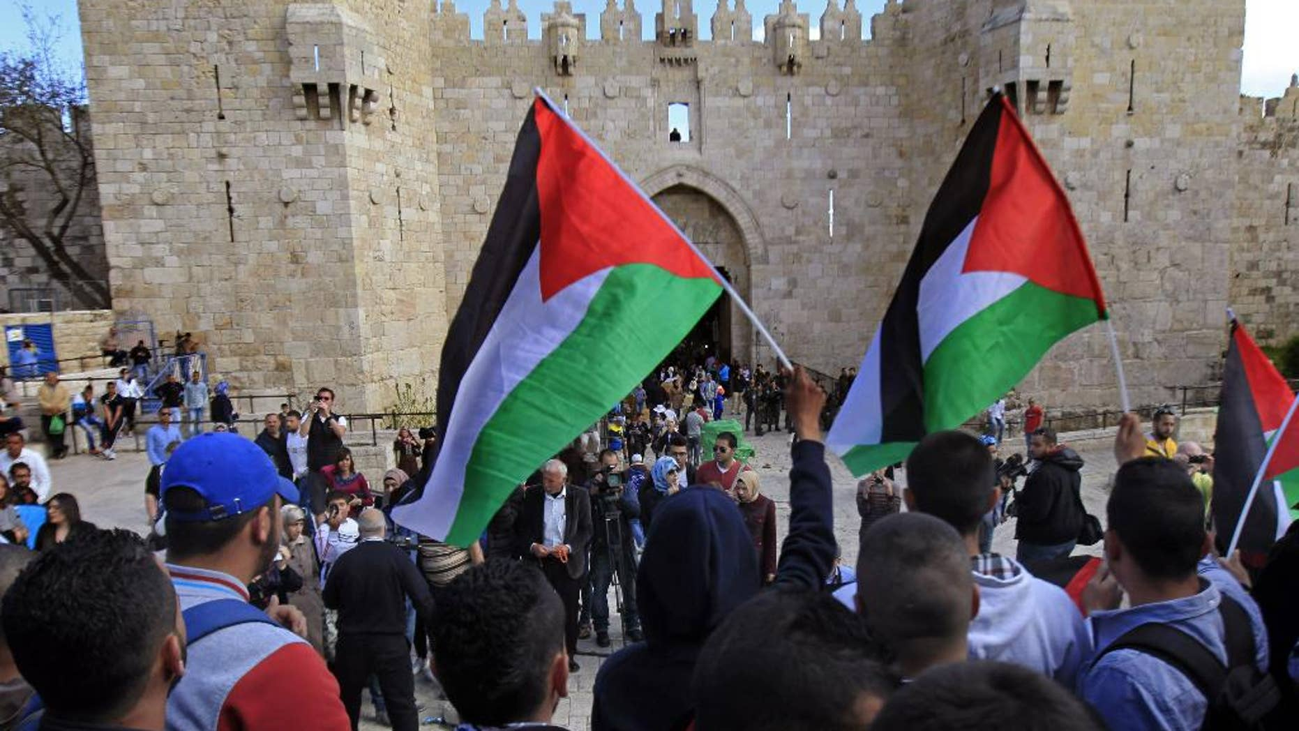 Palestinians carry national flags during a protest marking Land Day in front of the Damascus Gate in Jerusalem's Old City, Monday, March 30, 2015. Land Day commemorates riots on March 30, 1976, when six people were killed during a protest by Israeli Arabs whose property was annexed in northern Israel to expand Jewish communities. (AP Photo/Mahmoud Illean)