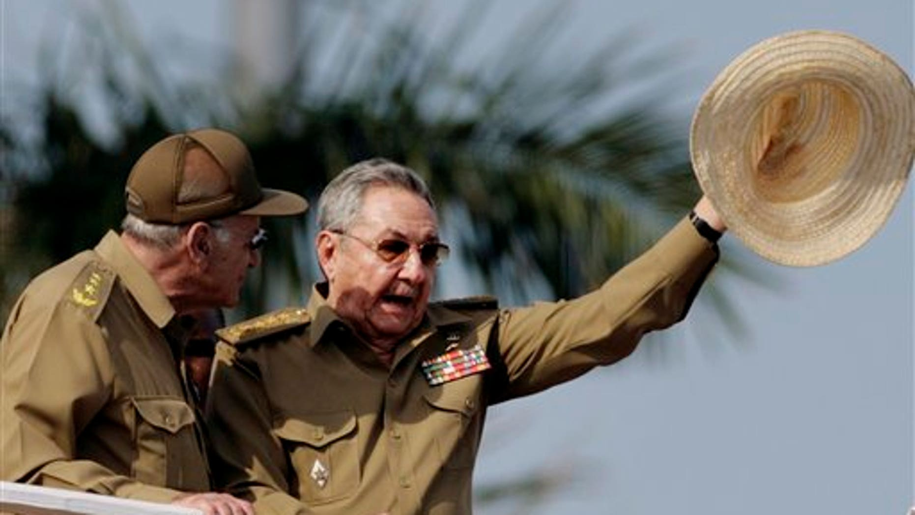 ALTERNATIVE CROP OF HAV121 - Cuba's President Raul Castro waves his hat during a military parade to commemorate the 50th anniversary of the Bay of Pigs failed invasion in Havana, Cuba, Saturday April 16, 2011. Cuba kicked off a crucial Communist Party congress Saturday with the parade to mark 50 years since the defeat of CIA-backed exiles at the Bay of Pigs.  At left is Vice President of the Council of State of Cuba and the Cuban Minister of the Interior Abelardo Colomé. (AP Photo/Javier Galeano)