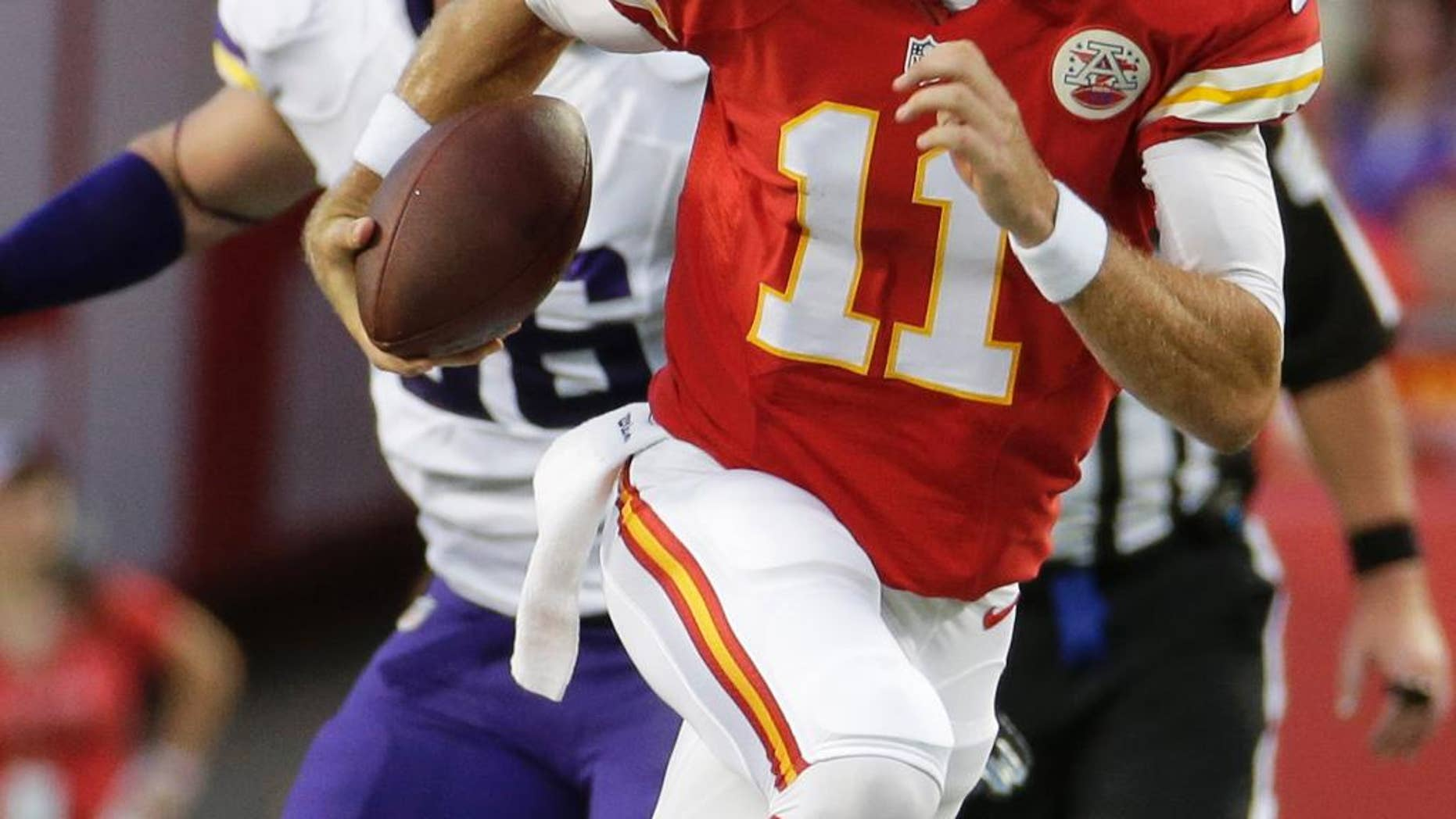 Kansas City Chiefs quarterback Alex Smith (11) runs past Minnesota Vikings defensive end Brian Robison during the first half of an NFL preseason football game in Kansas City, Mo., Saturday, Aug. 23, 2014. (AP Photo/Charlie Riedel)
