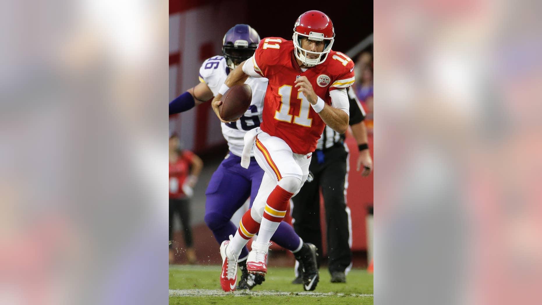 Kansas City Chiefs quarterback Alex Smith (11) runs past Minnesota Vikings defensive end Brian Robison during the first half of an NFL preseason football game in Kansas City, Mo., Saturday, Aug. 23, 2014. (AP Photo/Charlie Riedel)
