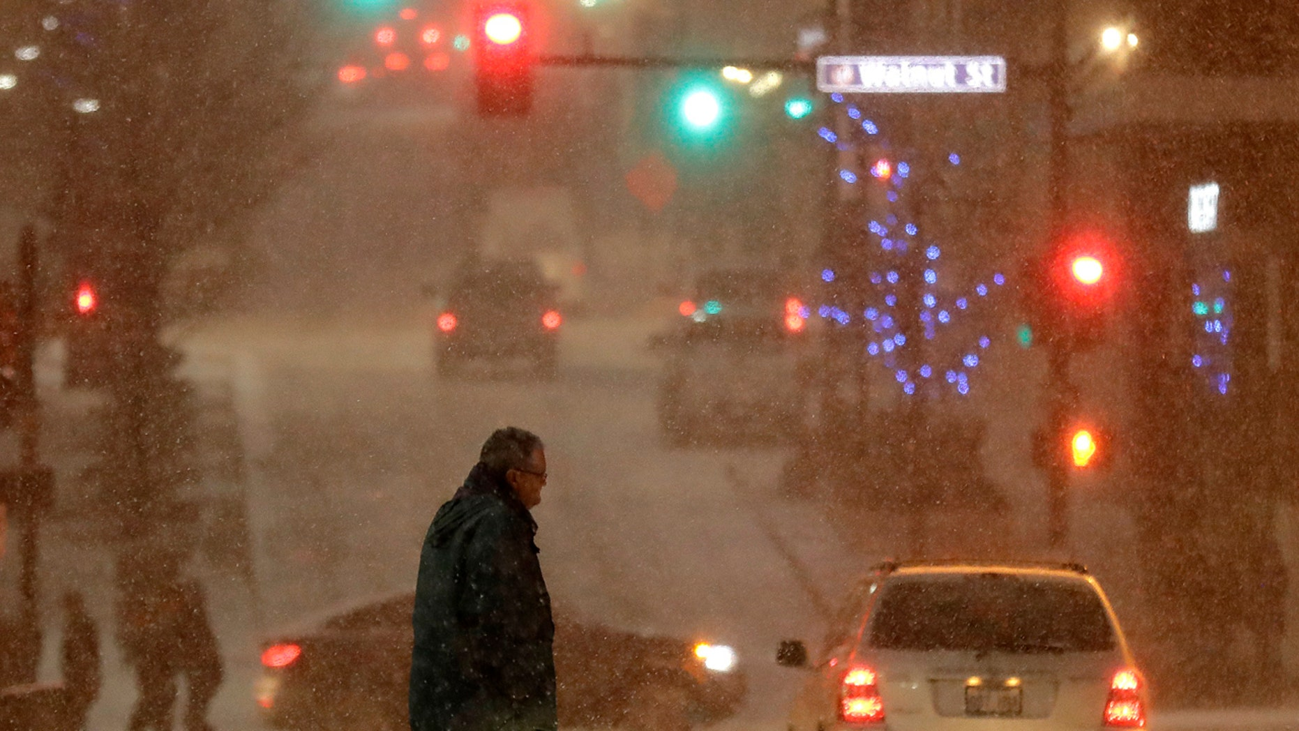 A pedestrian walks across a street in downtown Kansas City, Mo., on Saturday, Dec. 17, 2016.