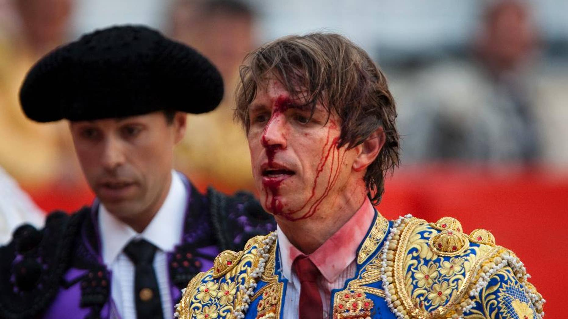 "FILE - In this April 25, 2010 file photo, bullfighter Manuel Diaz ""El Cordobes"", right, reacts after being gored by a bull during a bullfight at the Monumental Bullring in Barcelona, Spain. The southern Cordoba city court has held a hearing into a decades-old paternity dispute over whether two of Spain's most well-known bullfighters and who share the same showname, 'El Cordobes', are really father and son. The court began studying the claim Thursday April 28, 2016 by Manuel Diaz, 47 that he is the son of retired bullfighting legend Manuel Benitez, 79, something the elder torero has never recognized. (AP Photo/Emilio Morenatti, File)"